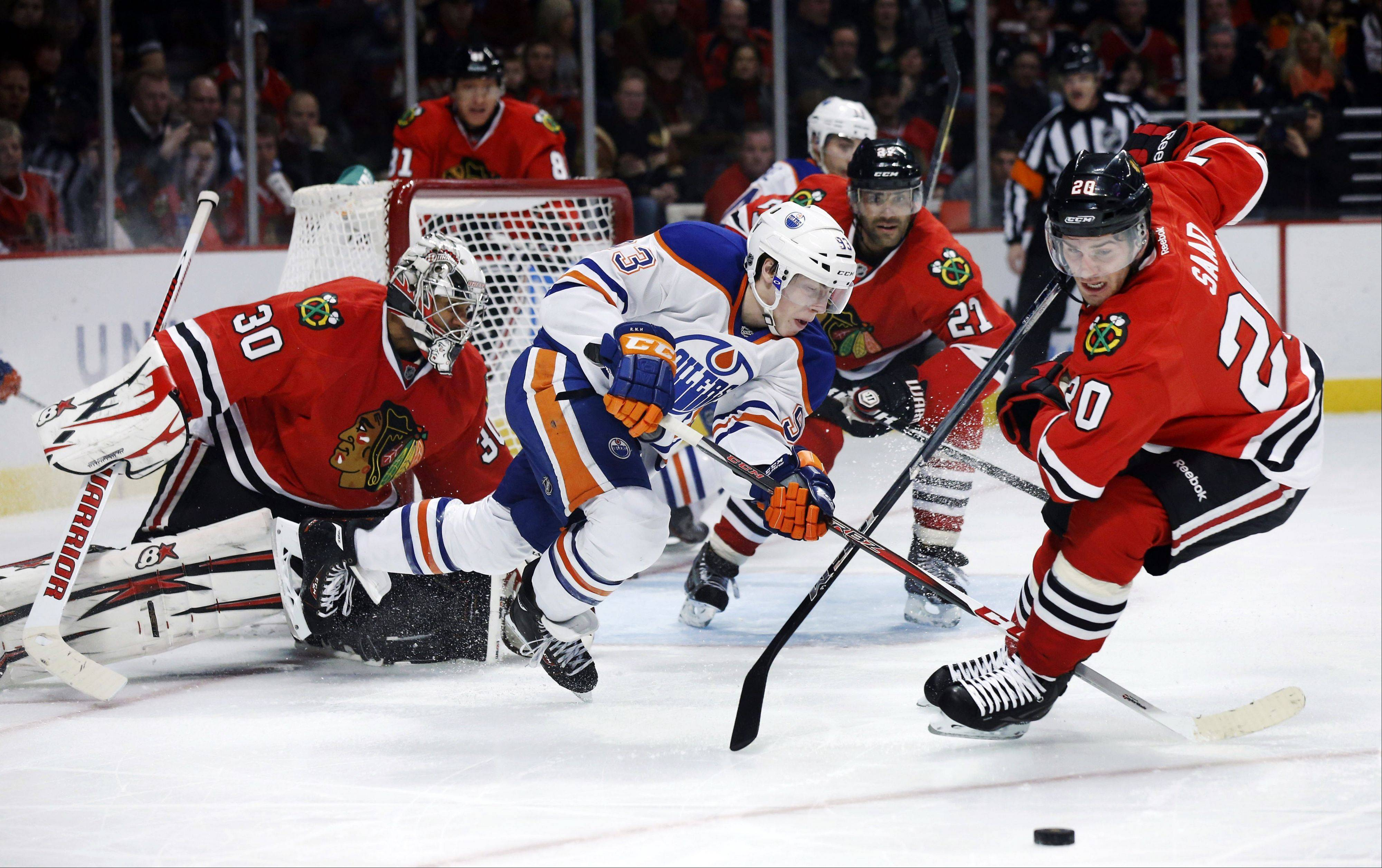 Edmonton Oilers forward Ryan Nugent-Hopkins is unable to get a rebound off Chicago Blackhawks goalie Ray Emery as left wing Brandon Saad clears the puck during the first period.