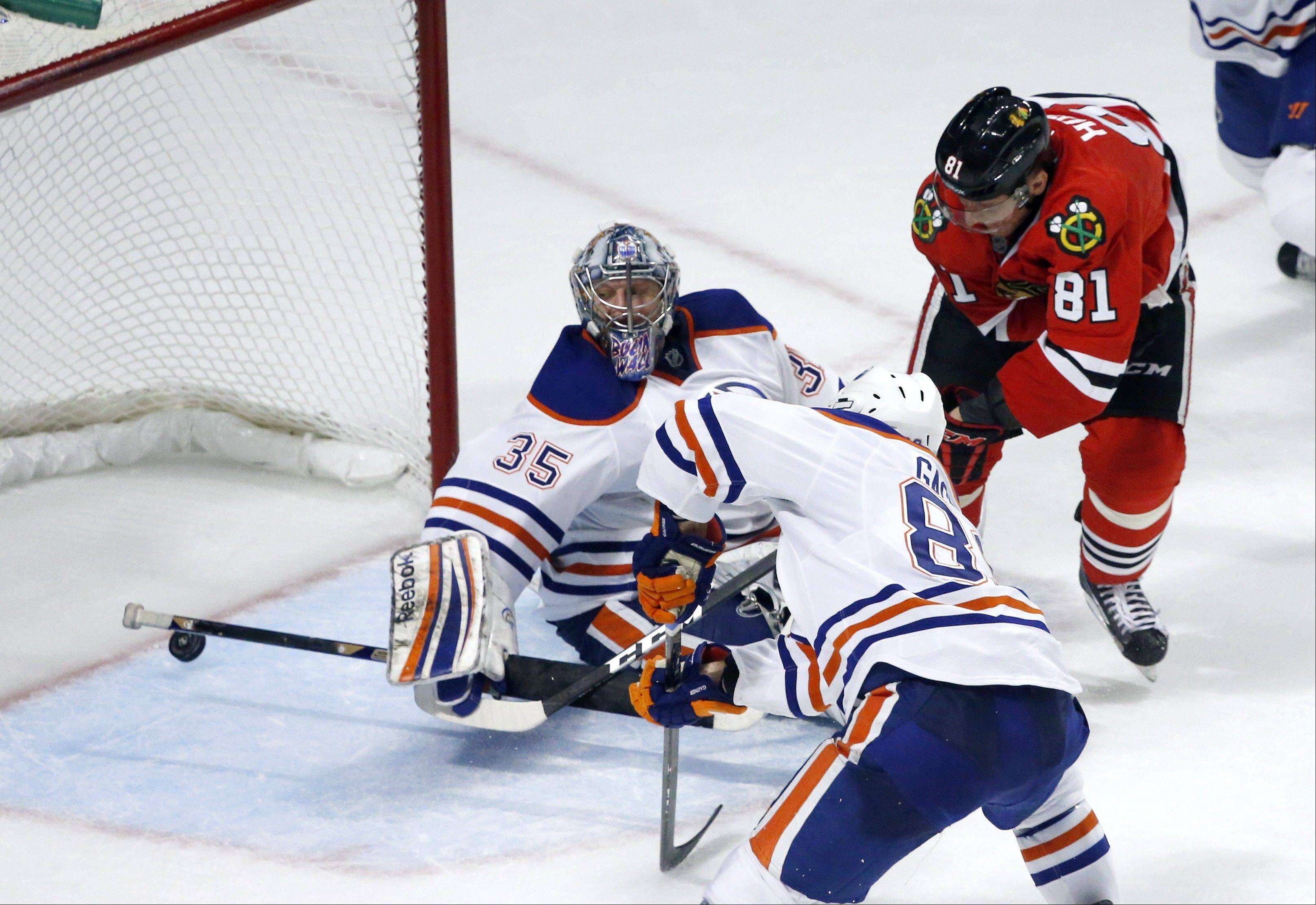 Chicago Blackhawks right wing Marian Hossa shoots the winning goal past Edmonton Oilers goalie Nikolai Khabibulin and center Sam Gagner during overtime.
