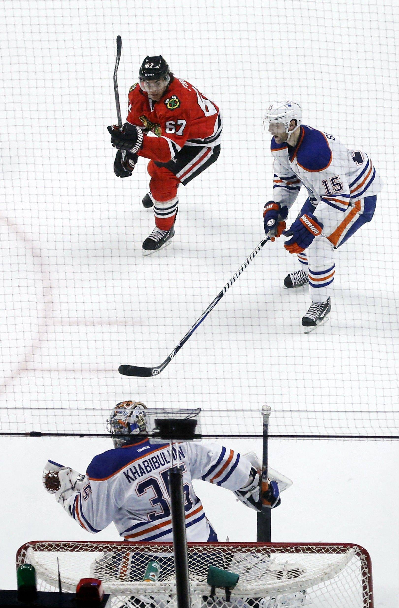 Edmonton Oilers goalie Nikolai Khabibulin makes a glove-save on a shot by Chicago Blackhawks center Michael Frolik as Oilers' Nick Schultz watches during the second period.