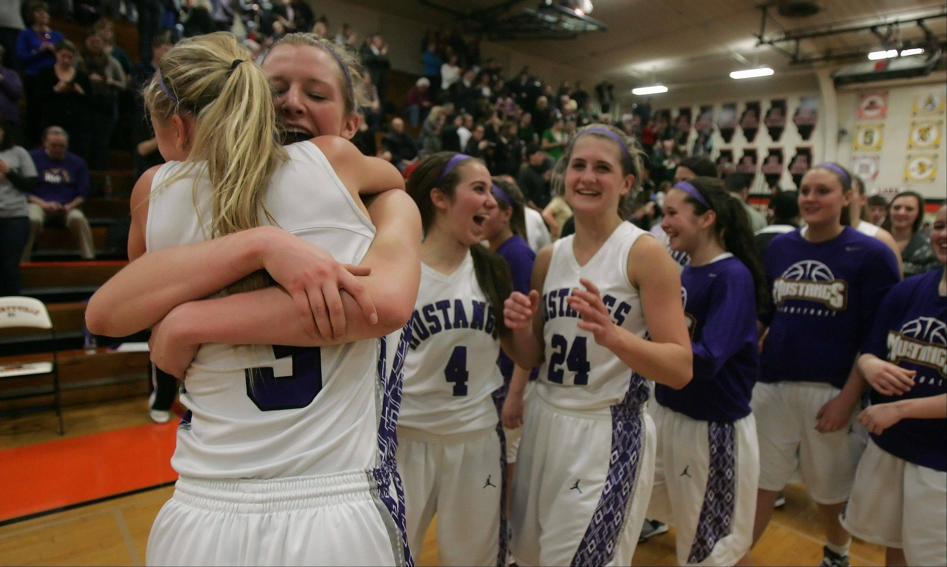 Rolling Meadows' Jackie Kempf, left, hugs Jenny Vliet after defeating Fremd in the Class 4A girls basketball sectional final at Libertyville High School Thursday.