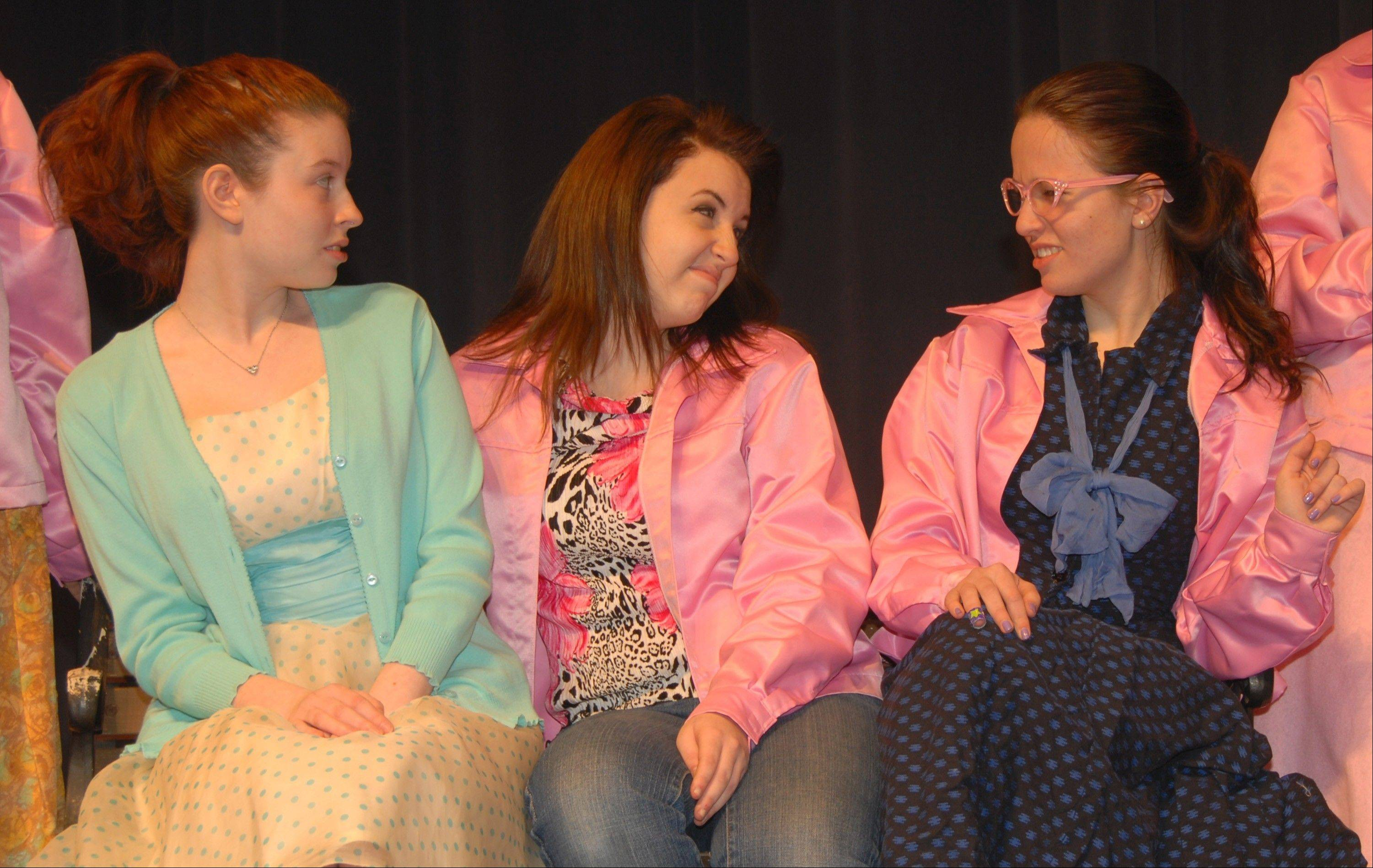 "In a scene from South Elgin High School's production of ""Grease,"" Sandy tries to fit in with the Pink Ladies. From left are Joelle Kasprisin, Haley Panico and Emmalee Gutowsky."