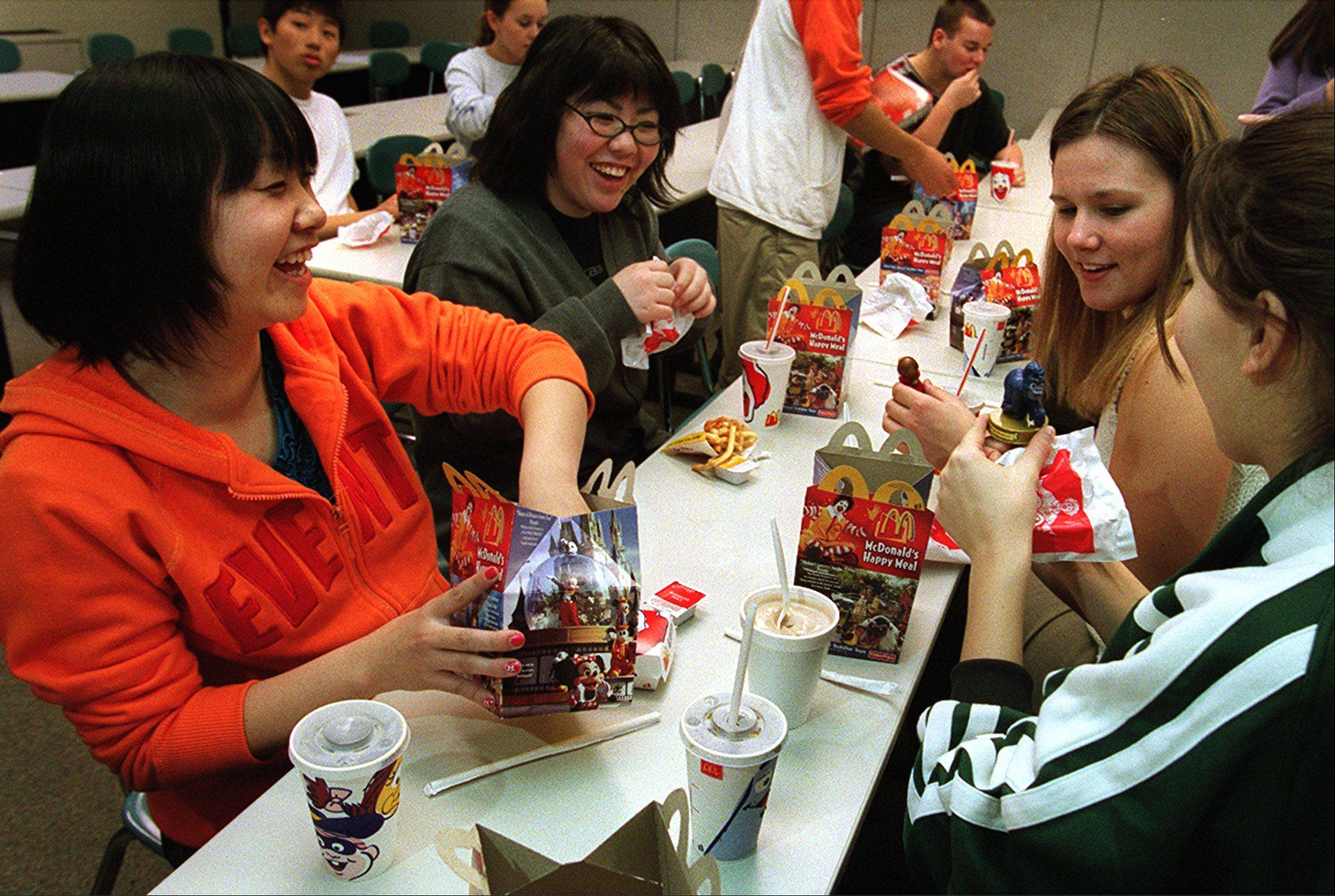 Japanese exchange students look at McDonald�s Happy Meal toys with Elk Grove student council members during the 2002 student exchange.