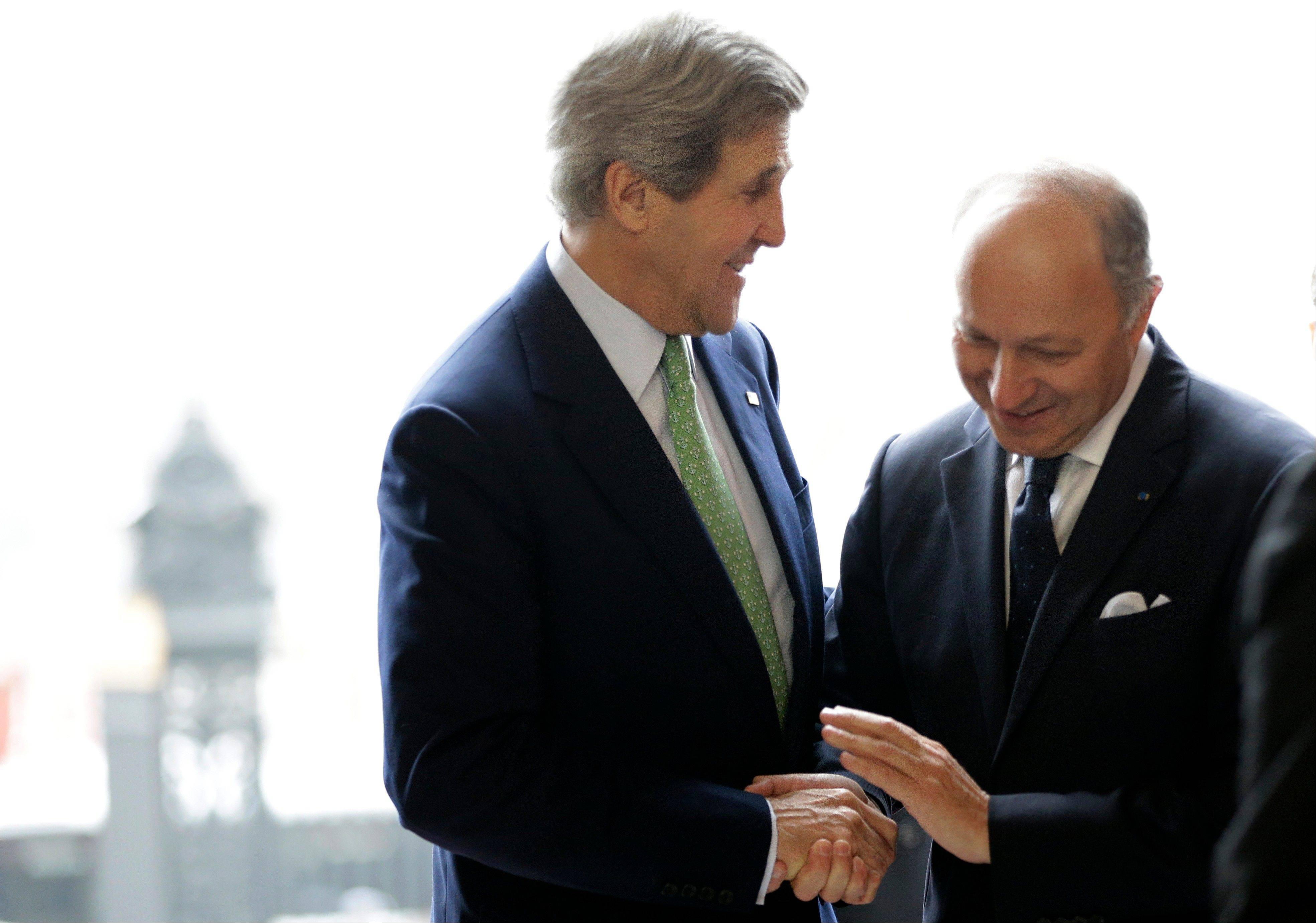 U.S. secretary of state John Kerry, left, is greeted Wednesday by French Minister of Foreign Affairs Laurent Fabius at the Foreign Ministry in Paris. Paris is the third leg of Kerry�s first official overseas trip, a hectic nine-day dash through Europe and the Middle East.