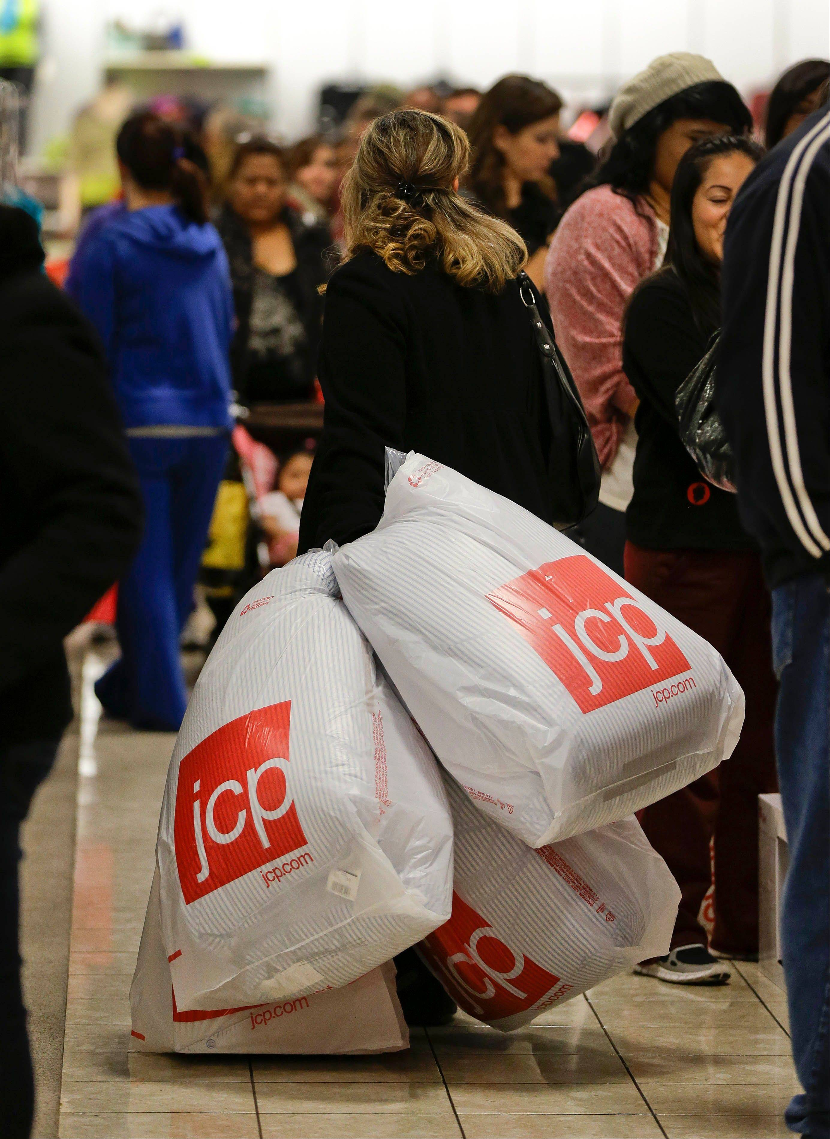 A shopper drags her purchases past a line of customers waiting to pay at a J.C. Penney store, in Las Vegas.