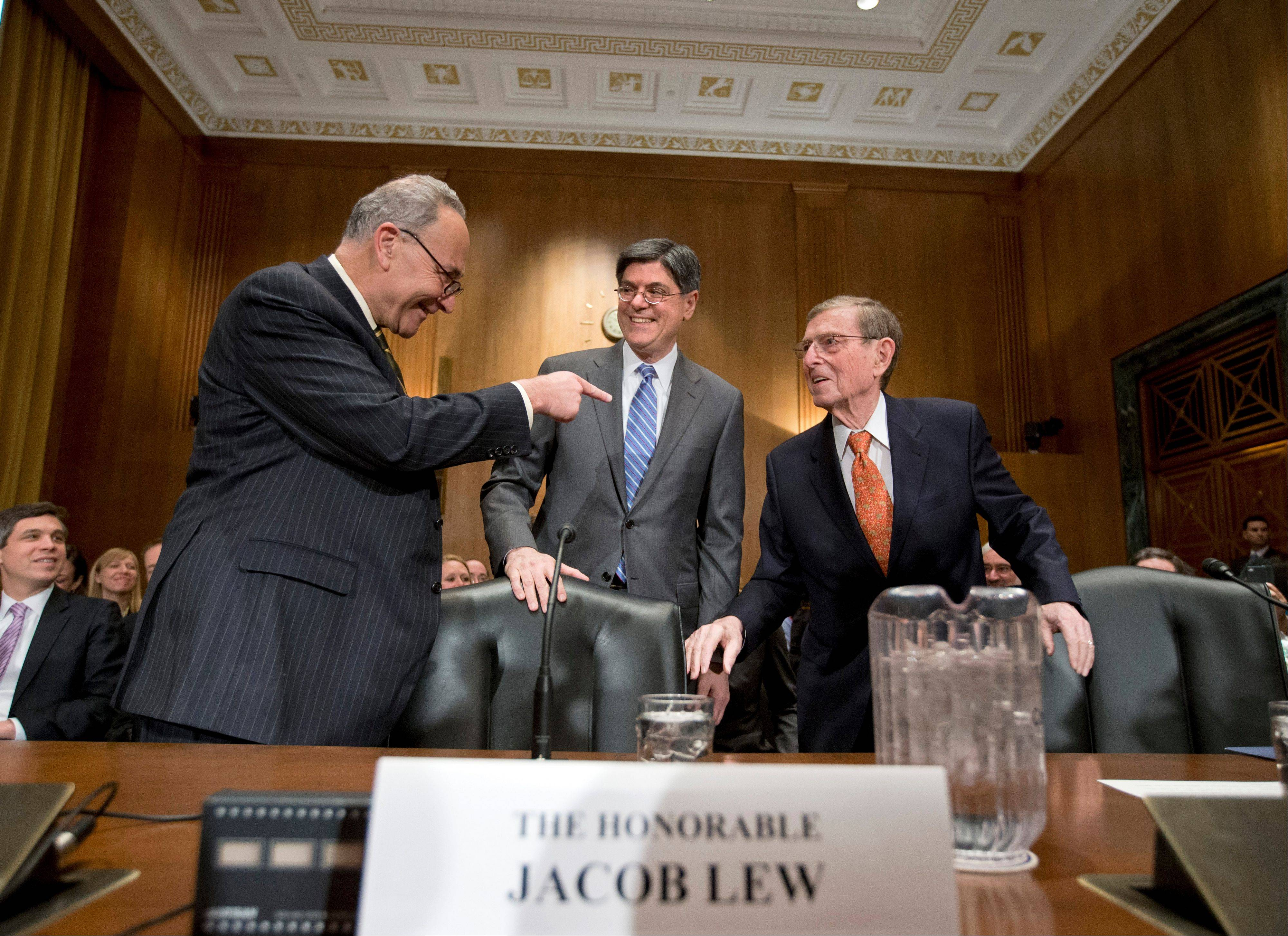 Jack Lew, President Obama's choice to be treasury secretary, center, talks with N.Y. Democratic Sen. Charles Schumer, left, and former New Mexico Sen. Pete Domenici.