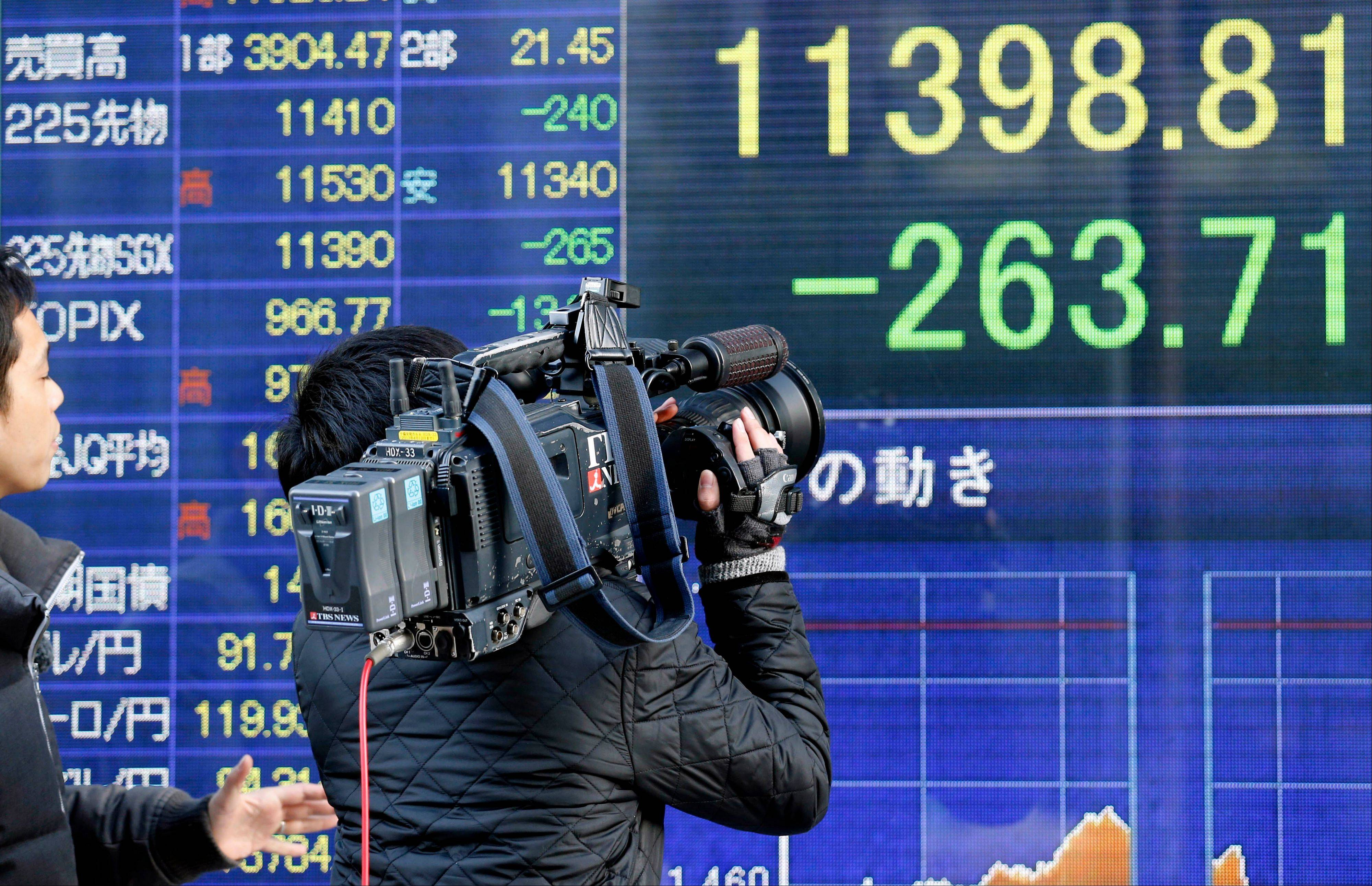 A TV cameraman films an electronic stock board flashing Nikkei 225 index Tuesday at a securities firm in Tokyo. Asian stock markets fell Tuesday amid anxiety about impending U.S. government spending cuts and the uncertain outcome of Italy's general election.