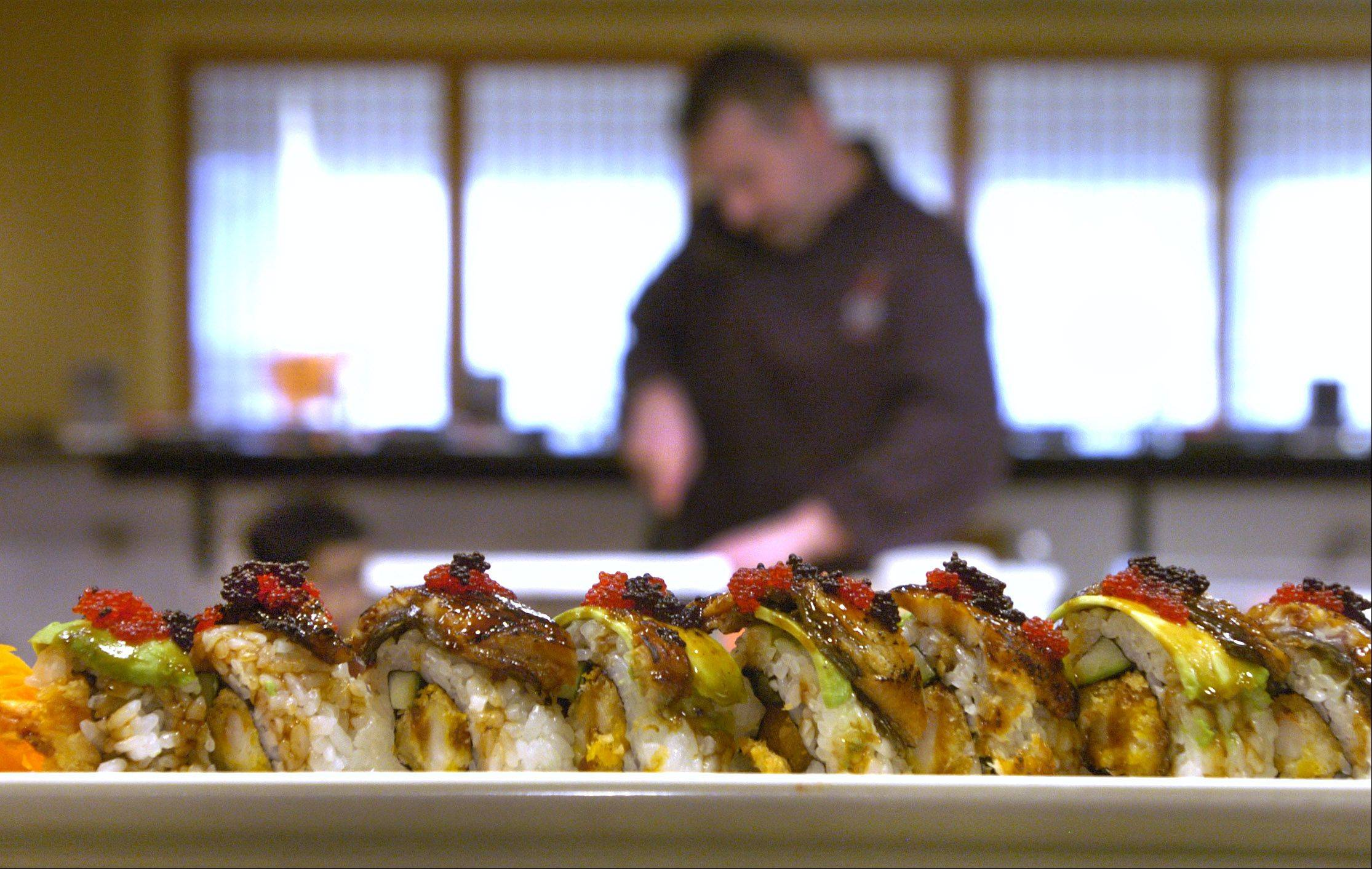 In the background, chef/owner Cliff Ostrowski prepares fruit sushi rolls for dessert; his eel sushi rolls are in the foreground.