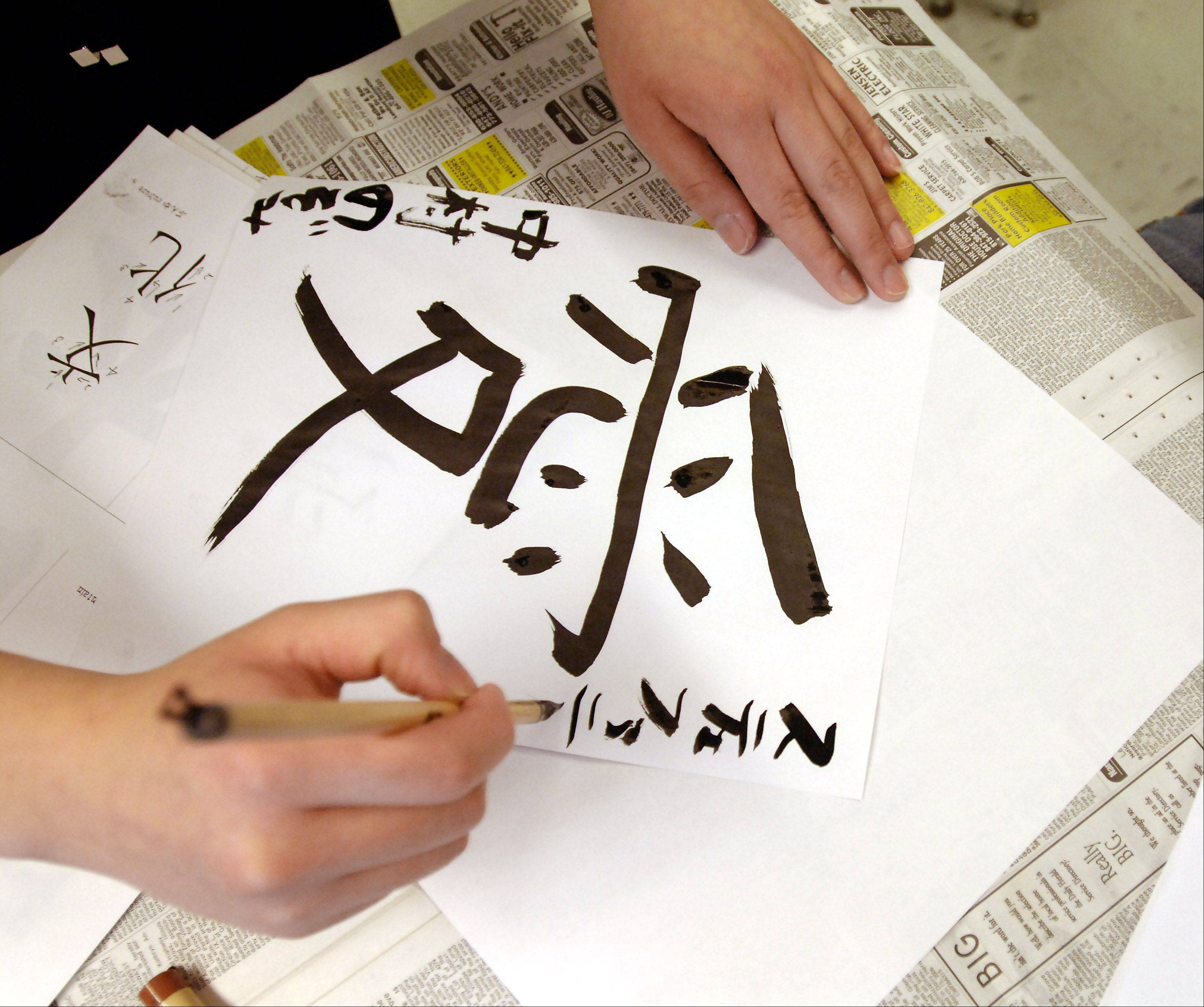 Mark Welsh/mwelsh@dailyherald.com 2006An Elk Grove High School student shows off her Japanese calligraphy skills during the 2006 student exchange.