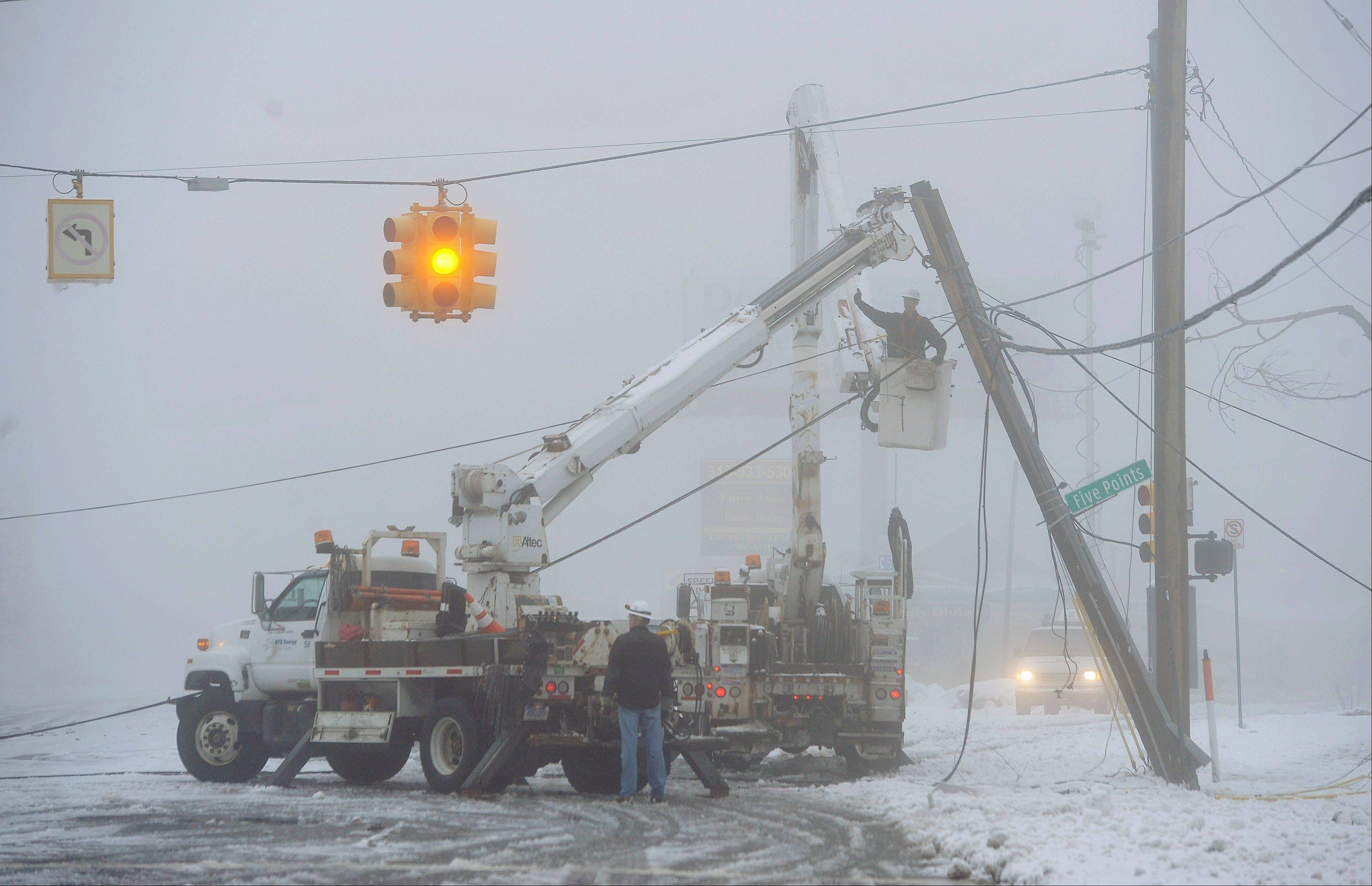 Fog shrouds work crews repairing down power lines Wednesday at 8 mile and Five points, in Southfield, Mich. The storm that hit the nation's midsection dropped at least 7 inches of snow on parts of Michigan and created dangerous driving conditions.