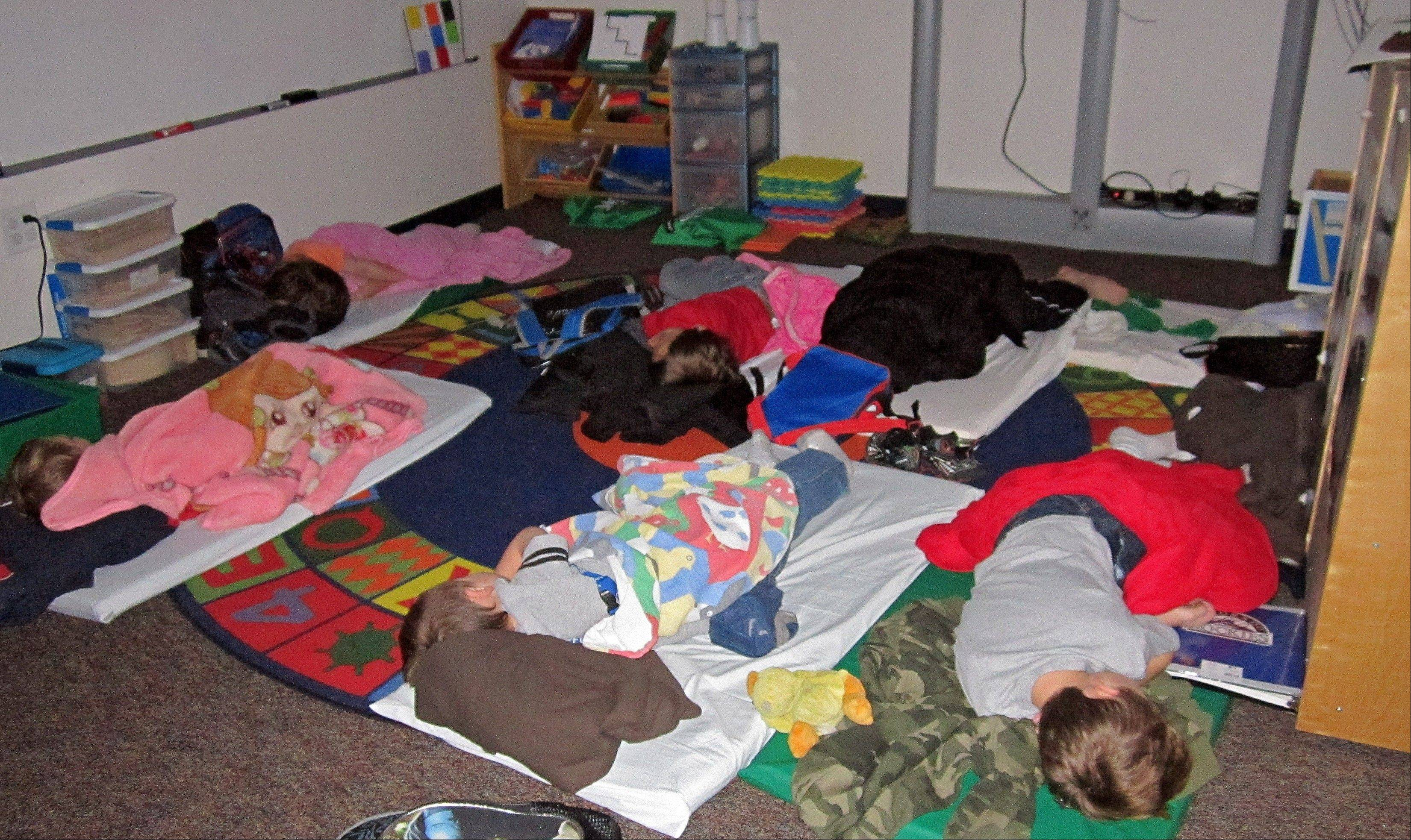 In this photo provided by Sharon Webb, principal of Miami-Yoder School, students sleep on the floor at the school on Wednesday in Yoder, Colo. About 60 students were forced to spend the night at the school after snow drifts closed roads in the area. The students went home later Wednesday after the roads were cleared.