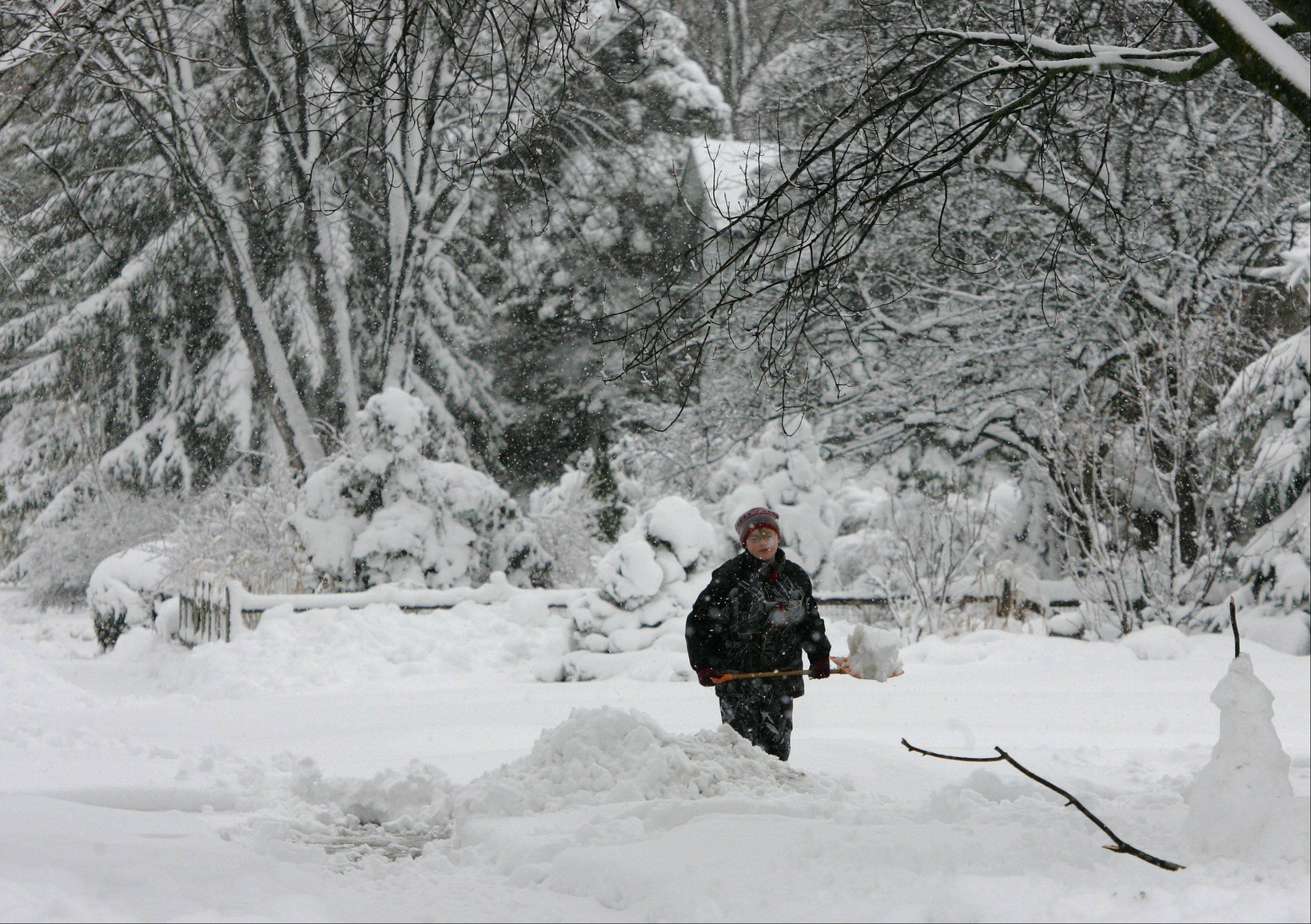 Oscar Tilford, 11, of Round Lake, shovels the driveway of his grandparents in Mundelein as area residents and businesses dig out Wednesday after a snowstorm pounded Lake County yesterday. Round Lake schools were closed for a snow day.