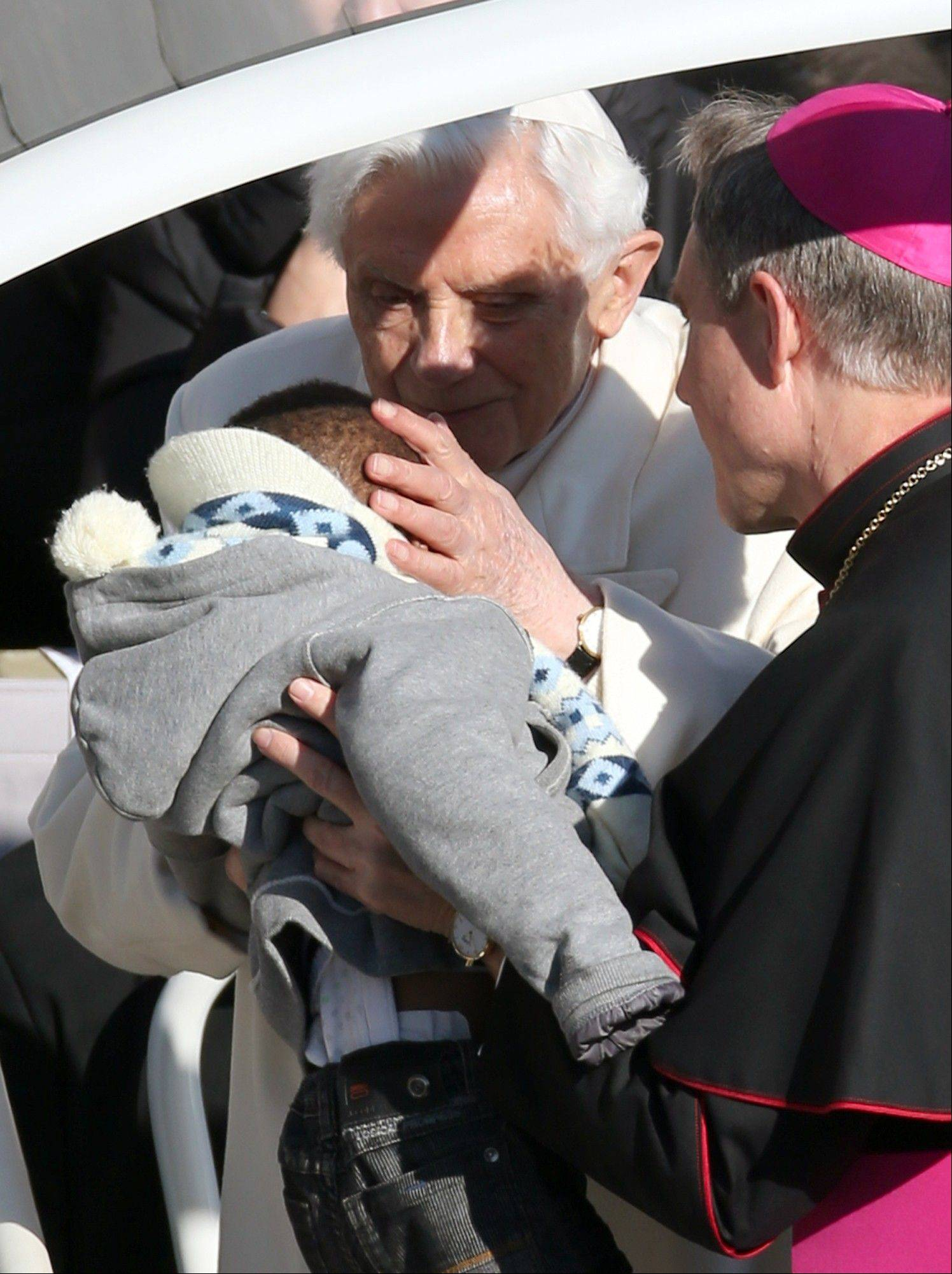 Pope Benedict XVI kisses a baby handed up to him by his secretary George Ganswein as he greets pilgrims in St. Peter's Square at the Vatican Wednesday, Feb. 27, 2013. Pope Benedict XVI greeted the Catholic masses in St. Peter's Square Wednesday for the last time before retiring, making several rounds of the square as crowds cheered wildly and stopping to kiss a half-dozen children brought up to him by his secretary.