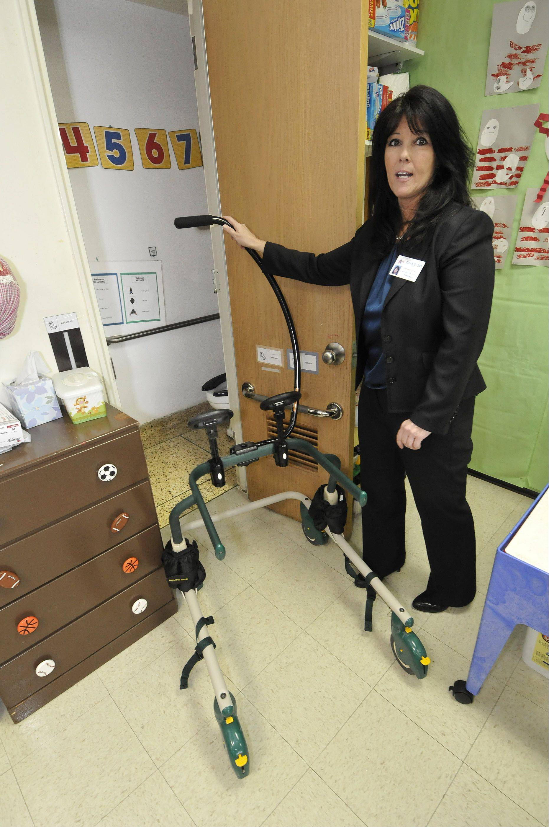 Jefferson Principal Stephanie Farrelly demonstrates how the door to a classroom's restroom isn't wide enough to accommodate a student's walker.