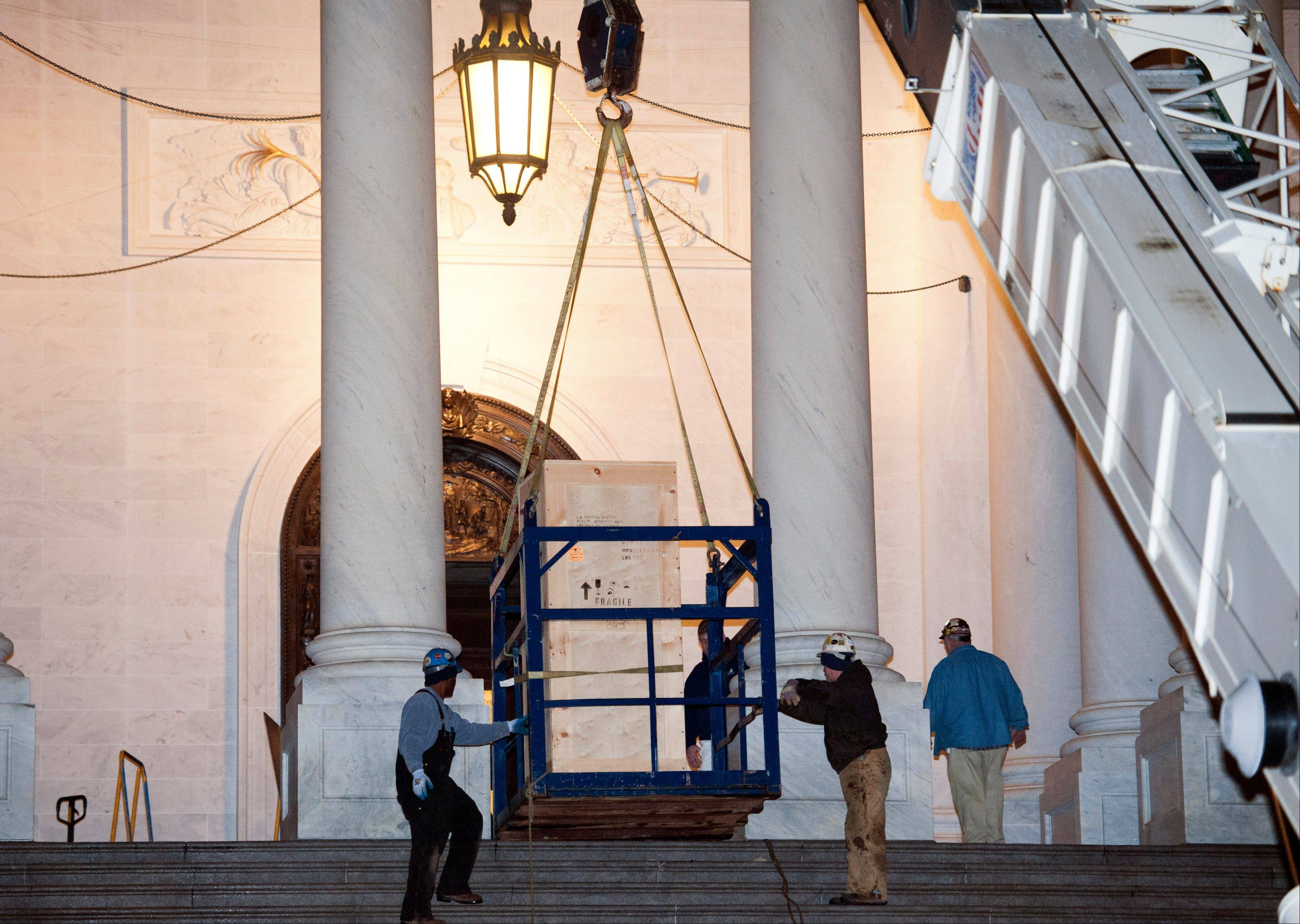 Riggers stabilize the basket on the crate containing the bronze statue of Rosa Parks Friday as it is delivered to the U.S. Capitol's Memorial Door by a crane.