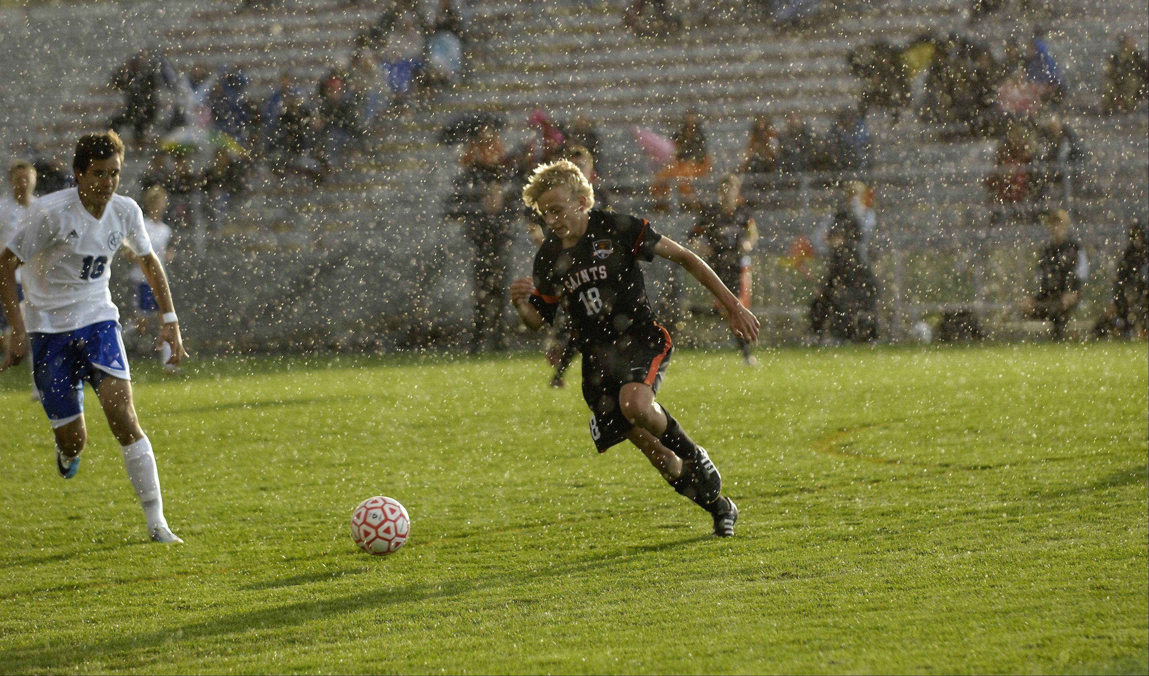 A heavy rain starts to fall as St. Charles East's Kevin Heinrich dribbles the ball through the midfield during a 2011 game at Batavia High School. A proposal to install artificial turf has been made.