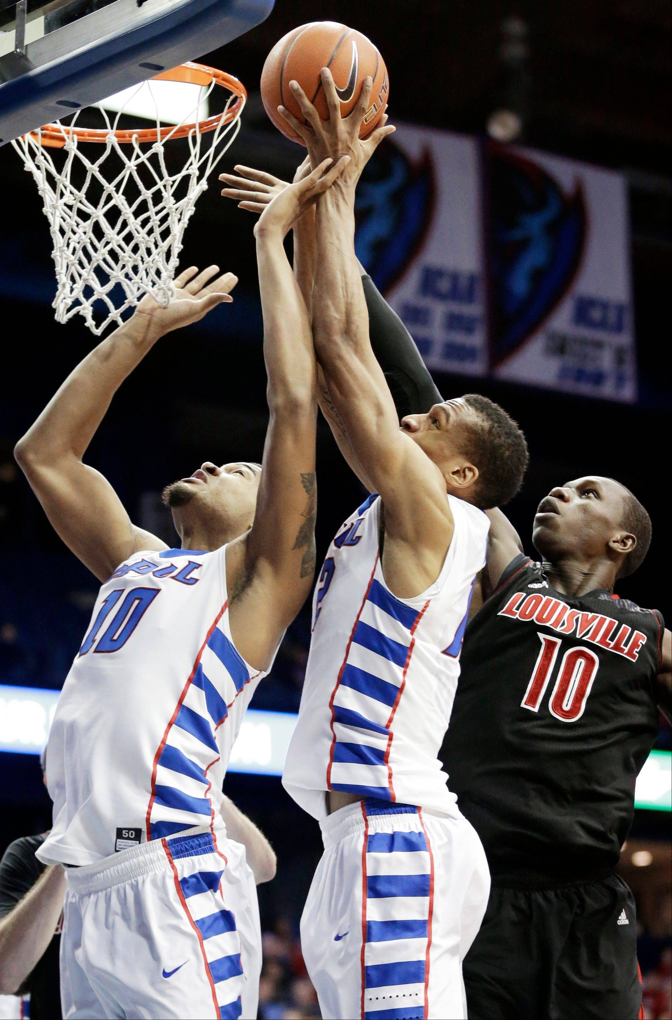 DePaul forward Cleveland Melvin, center, battles for a rebound with center Derrell Robertson Jr., left, and Louisville center Gorgui Dieng, of Senegal, during the second half of an NCAA college basketball game in Rosemont, Ill., on Wednesday, Feb. 27, 2013. Louisville won 79-58.