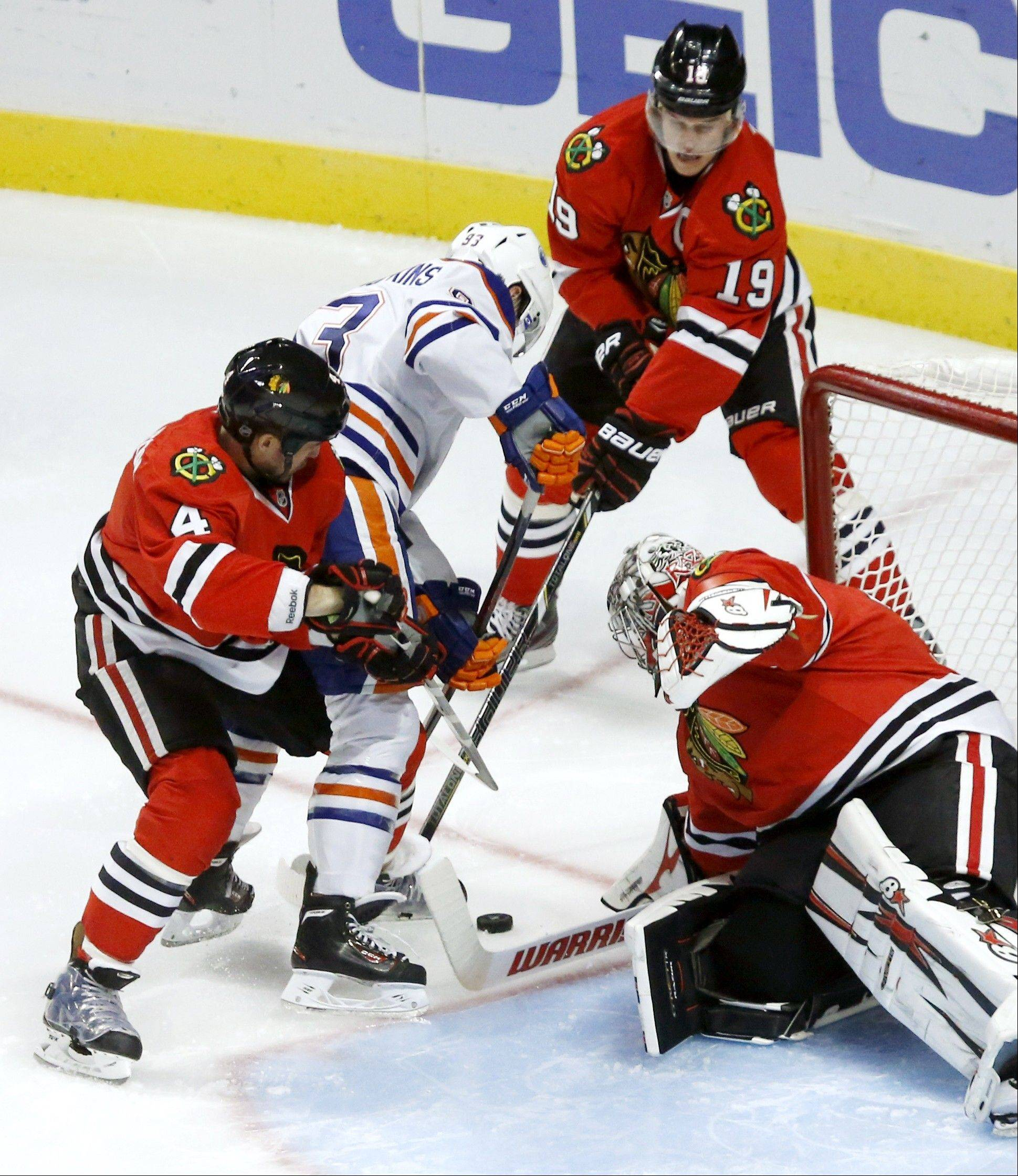 The Blackhawks' Niklas Hjalmarsson (4) and Jonathan Toews (19) keep Oilers center Ryan Nugent-Hopkins from getting a shot on goalie Ray Emery during the third period Monday night at the United Center. The Blackhawks won 3-2 in overtime.