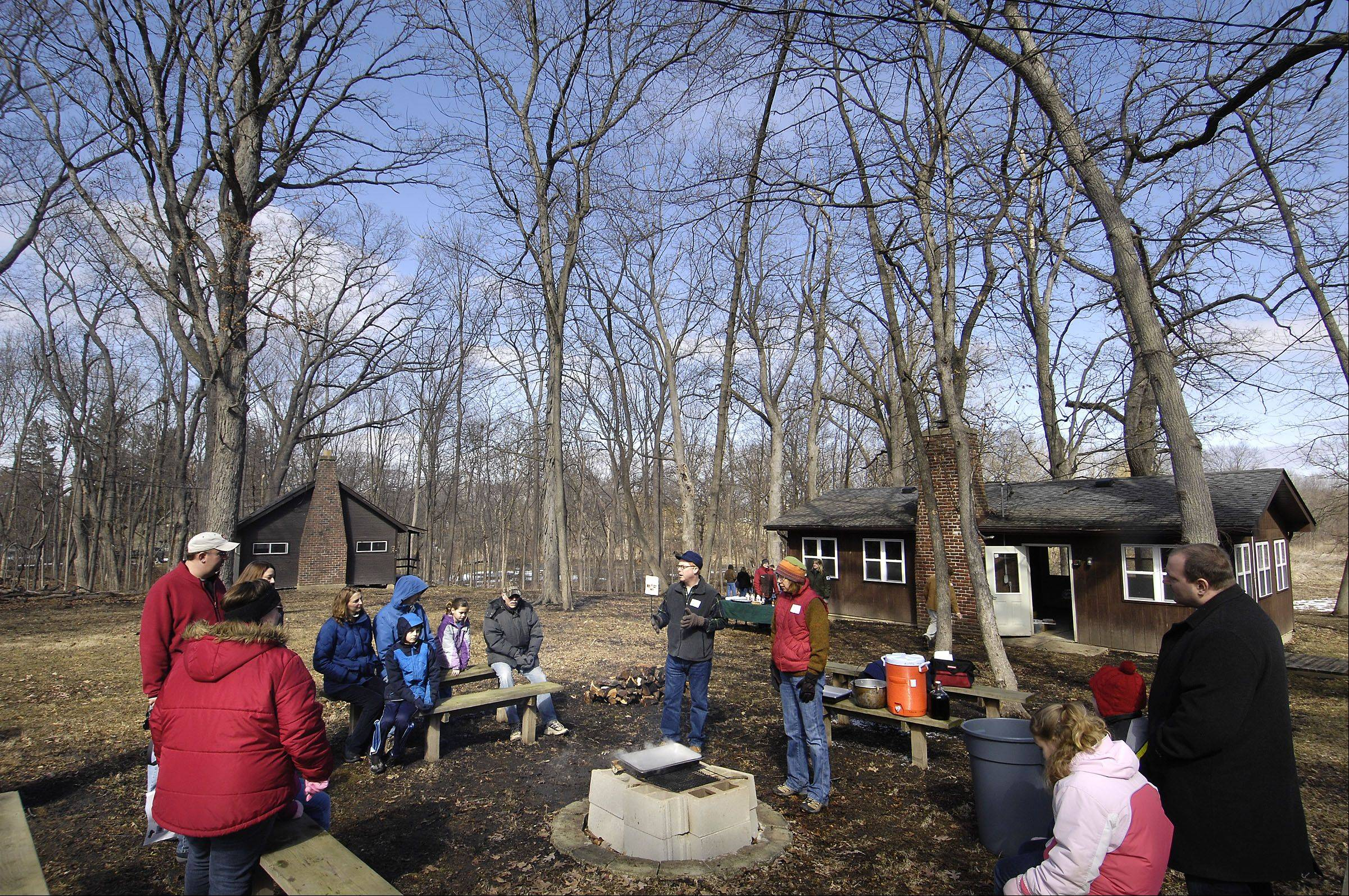Ken King of St. Charles and Sue Everson of Elgin explain the process of simmering maple sap Sunday at Maple Sugaring Days event at Brewster Creek Forest Preserve in St. Charles. The annual education event was staffed by volunteers for the Forest Preserve District of Kane County.