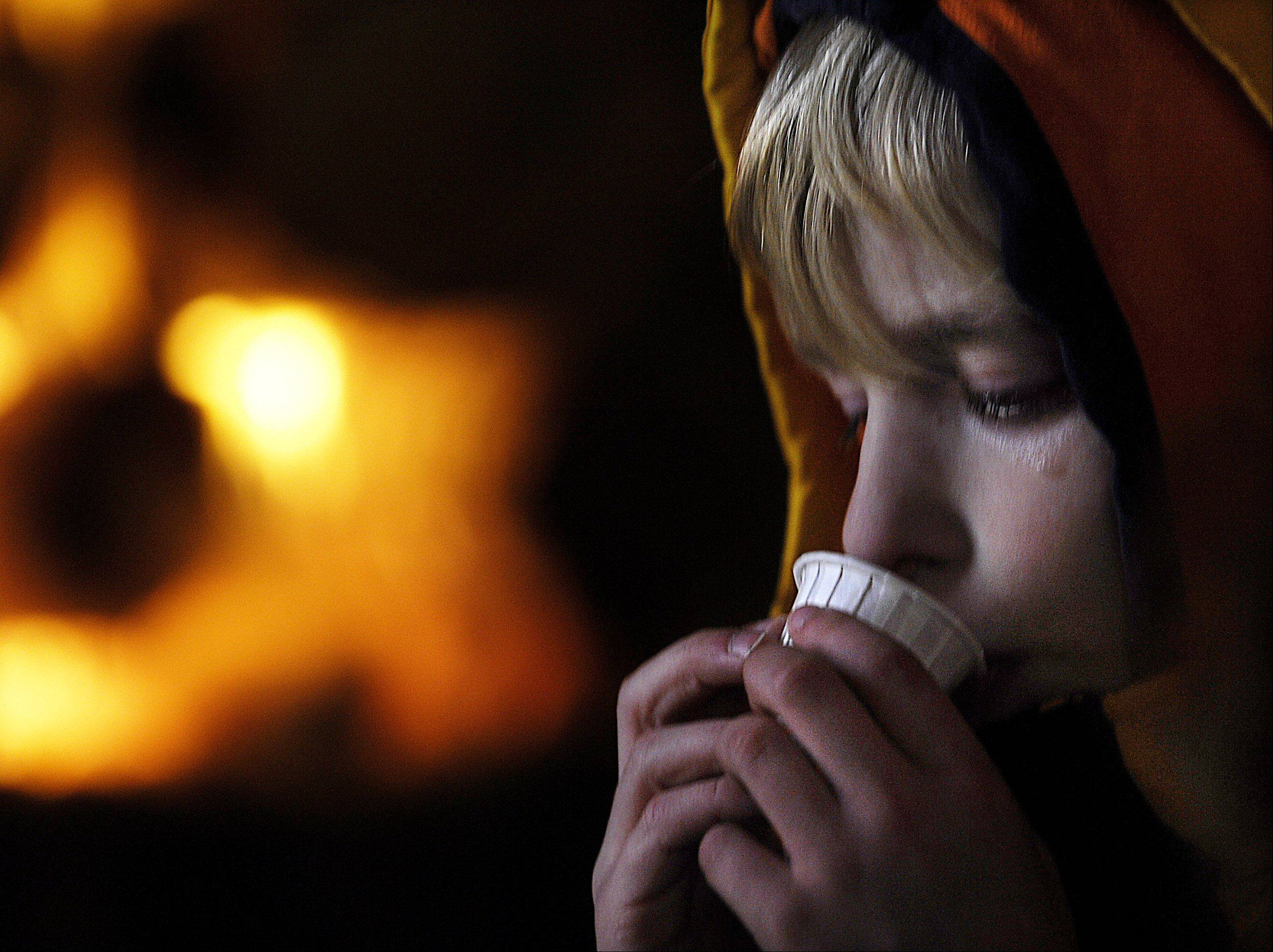 Oberon Scheeler, 7, sips pure maple syrup near a fireplace in the Sugar House during the McHenry County Conservation District's Festival of the Sugar Maples at Coral Woods near Marengo. Oberon was with his sister Tatiana, 4, and mother Renee of Elgin.