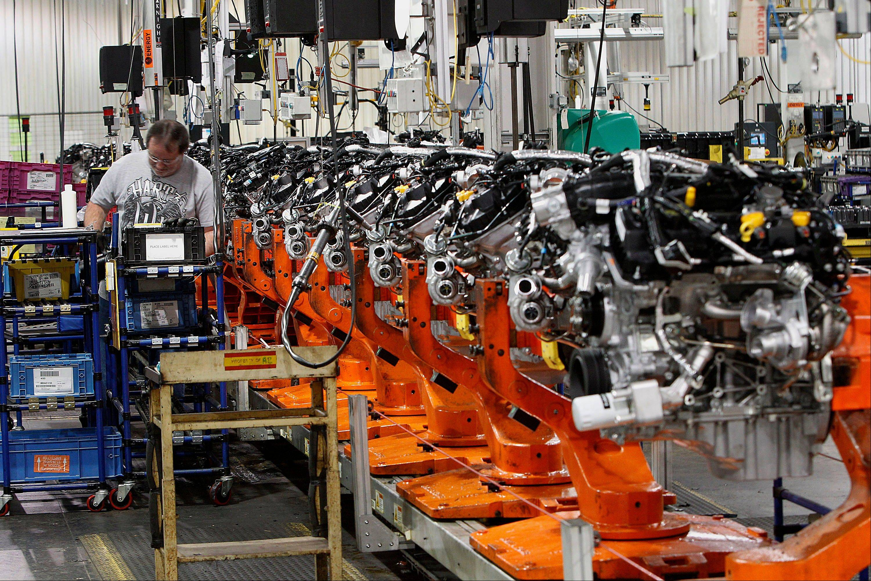 Employee Cliff McCloskey assembles an 2.0 liter ecoboost engines last Feb. 21 on the production line at the Ford Motor Co. Cleveland Engine Plant in Brook Park, Ohio.