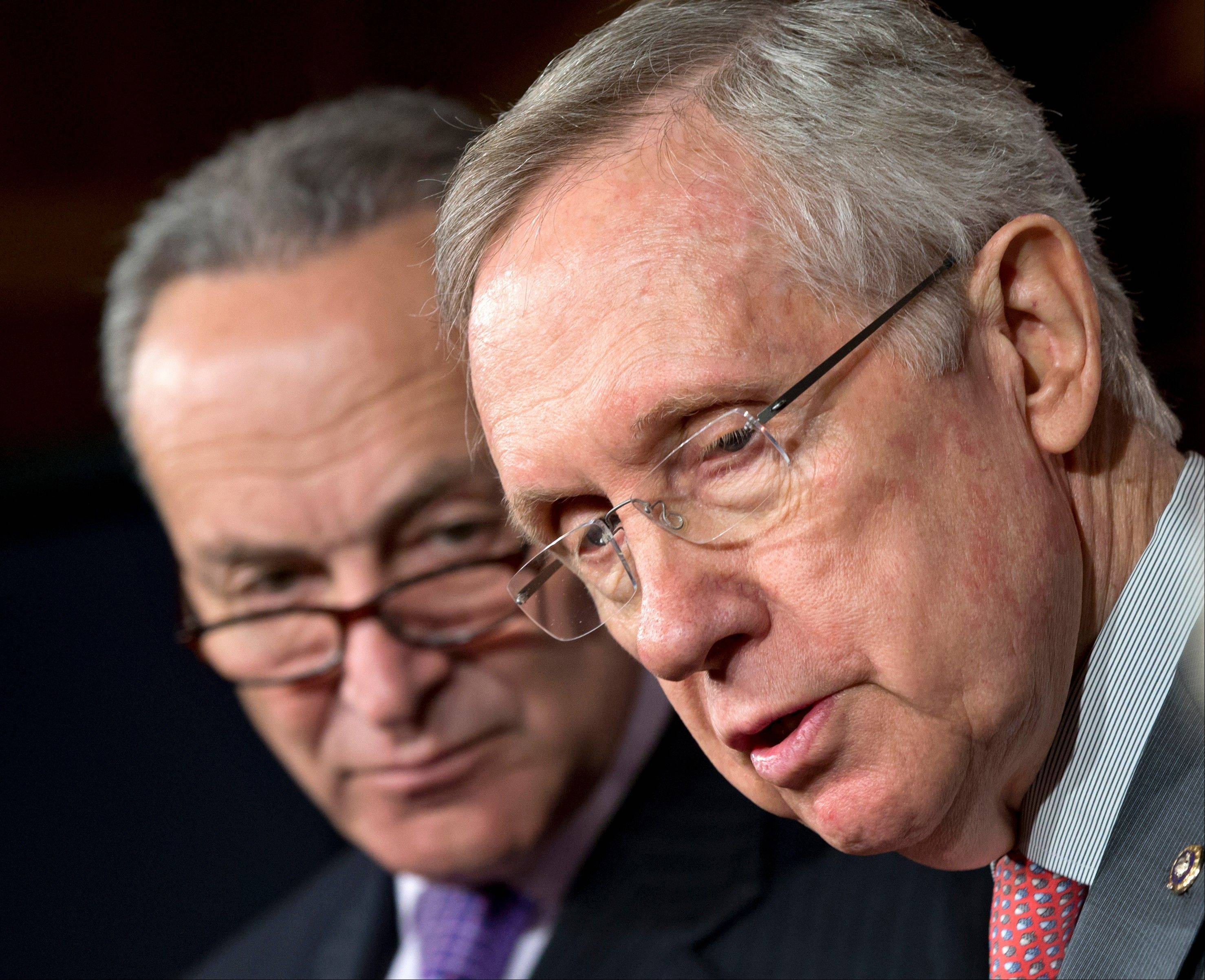Senate Majority Leader Harry Reid of Nev., right, accompanied by Sen. Charles Schumer, a New York Democrat, faces reporters on Capitol Hill Thursday to talk about the impending automatic spending cuts that would take effect Friday.