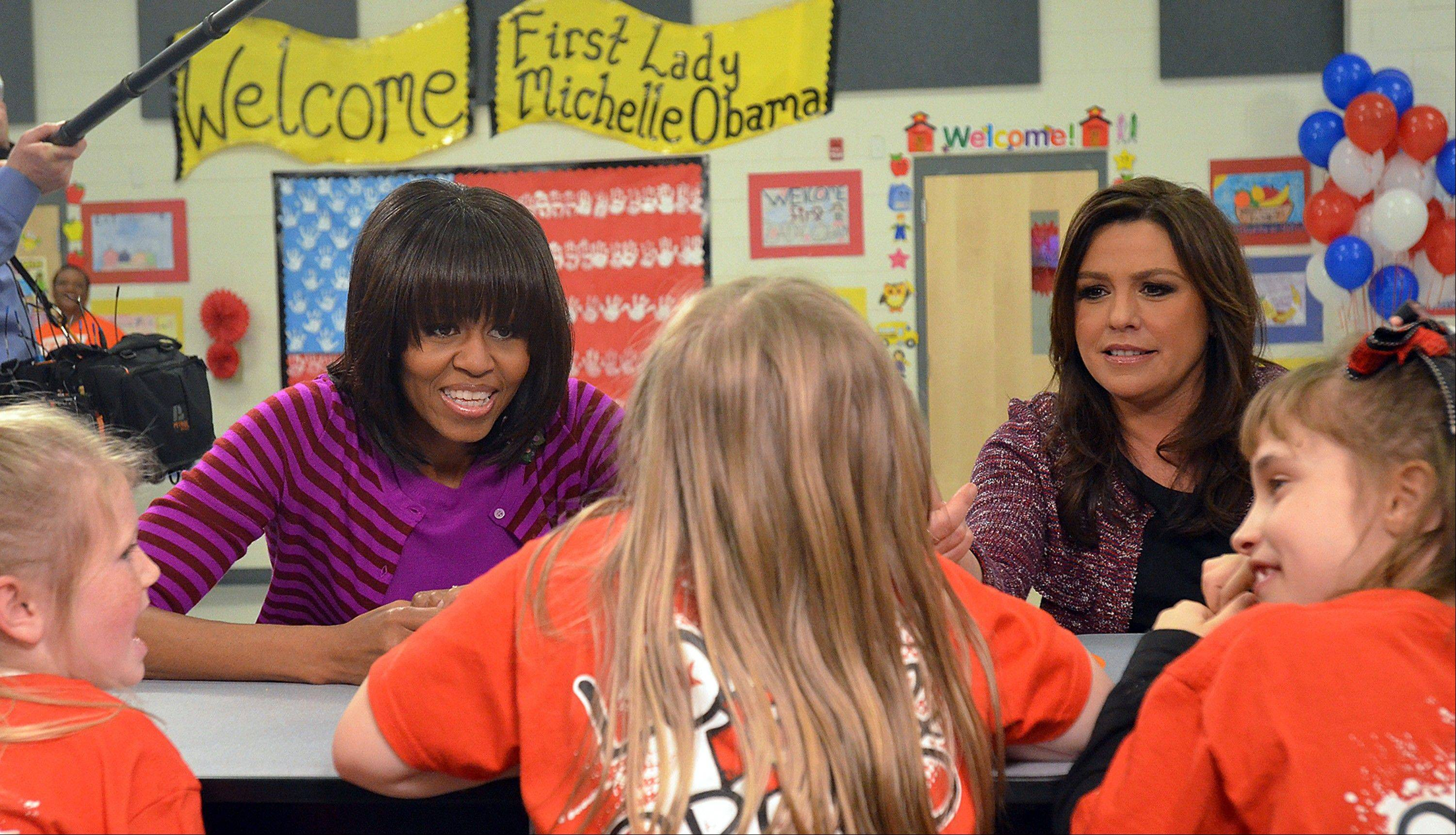 "First Lady Michelle Obama, left, and television personality Rachel Ray, talk to students from Northside and Eastside Elementary Schools in Clinton, Miss., during a stop for the ""Let's Move!"" initiative at the schools Wednesday, Feb. 27, 2013. (AP Photo/The Clarion-Ledger, Rick Guy)"