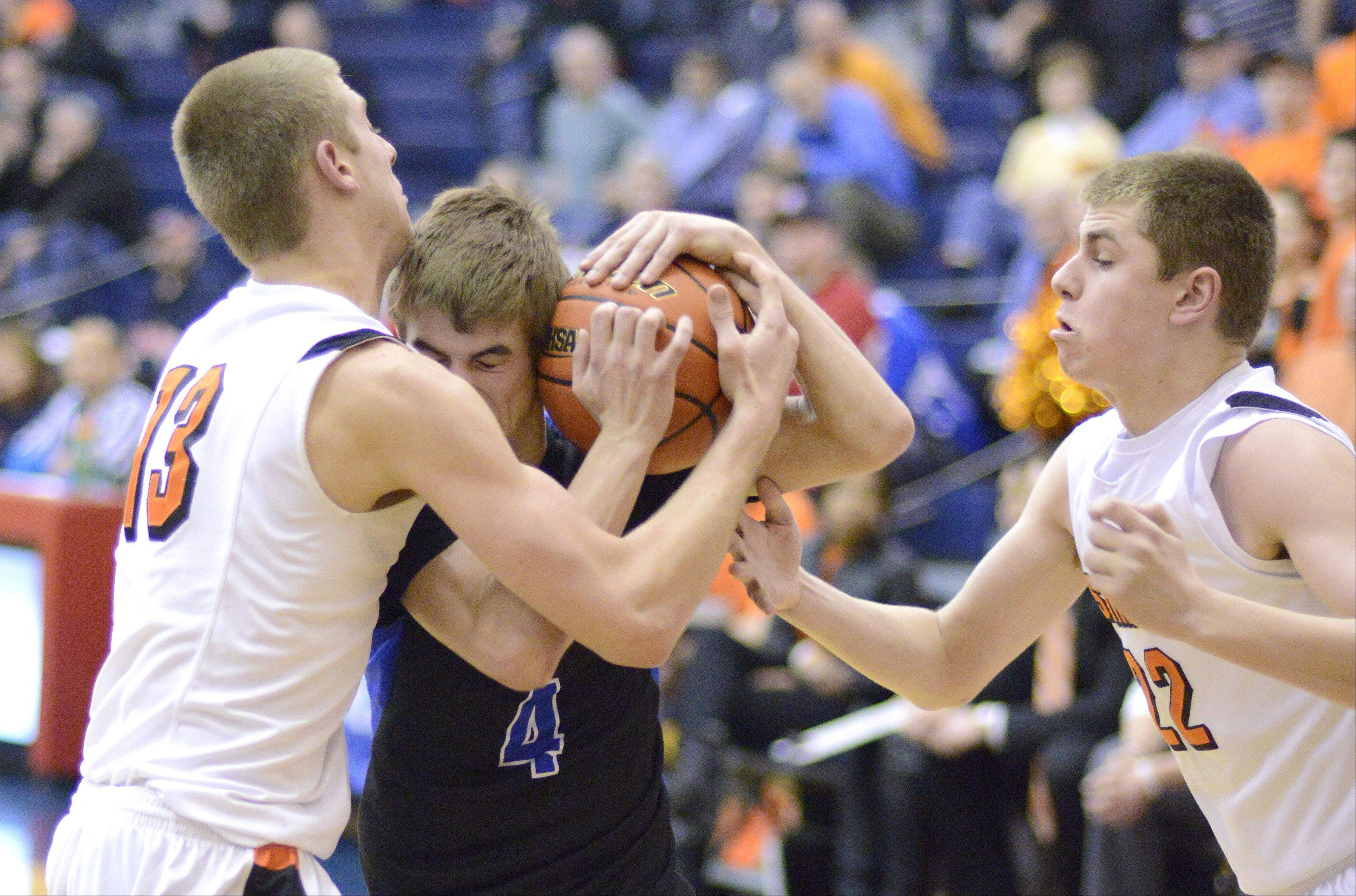 St. Charles North's Jake Ludwig wrestles with St. Charles East's Ben Skoog and James McQuillan until a foul is called on the Saints in the third quarter of the Class 4A regional on Wednesday, February 27. St. Charles North will play Larkin Friday.