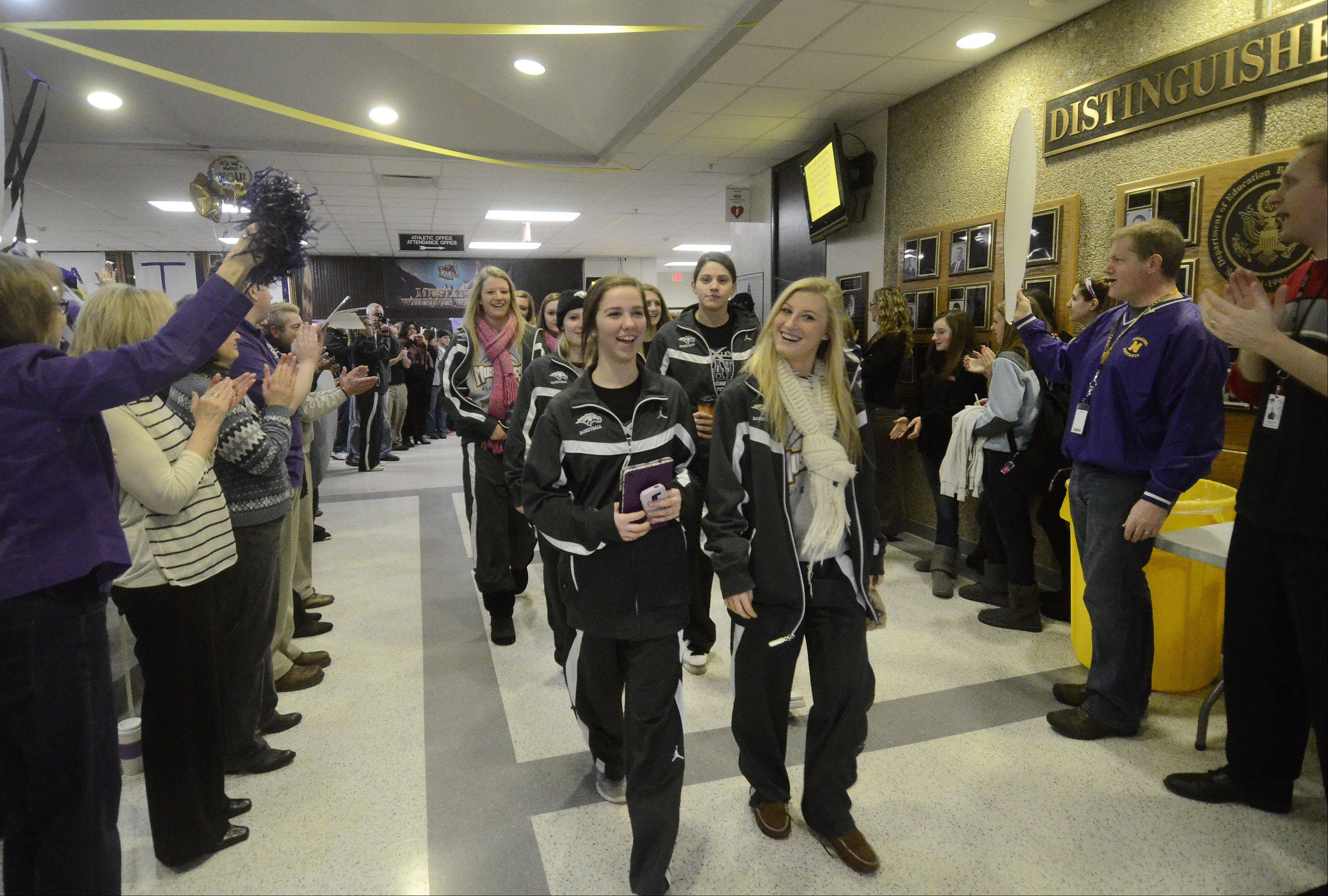 Sami Kay, left, and Jackie Kemph lead the Rolling Meadows girls basketball team as they are sent off with a school rally and head to Bloomington for their first appearance in the state championship.