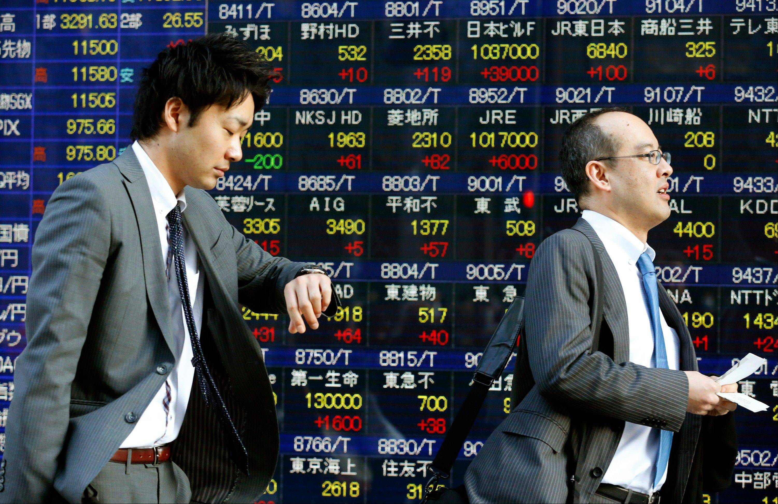 A man looks at his watch Thursday while walking in front of an electronic stock indicator in Tokyo. Asian stock markets rose Thursday as positive economic indicators and the nomination of a pro-stimulus Bank of Japan chief bolstered hopes for faster growth. The Nikkei 225 stock average closed at 11,559.36, up 2.7 percent.