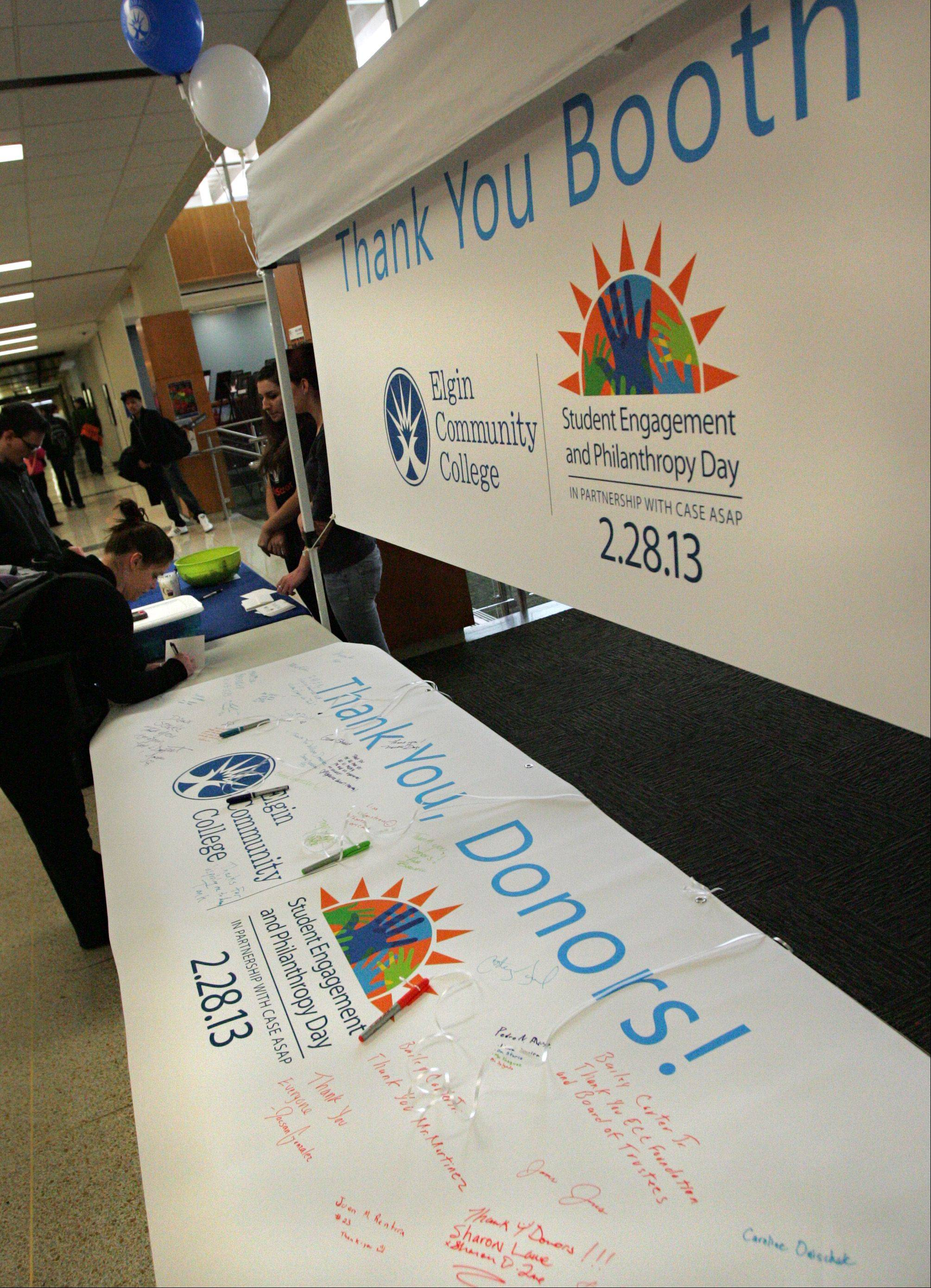 Elgin Community College students signed a large banner during the first Student Engagement and Philanthropy Day, thanking those who made their education possible. They day's events also included a session on philanthropic giving, which includes donating time and money.