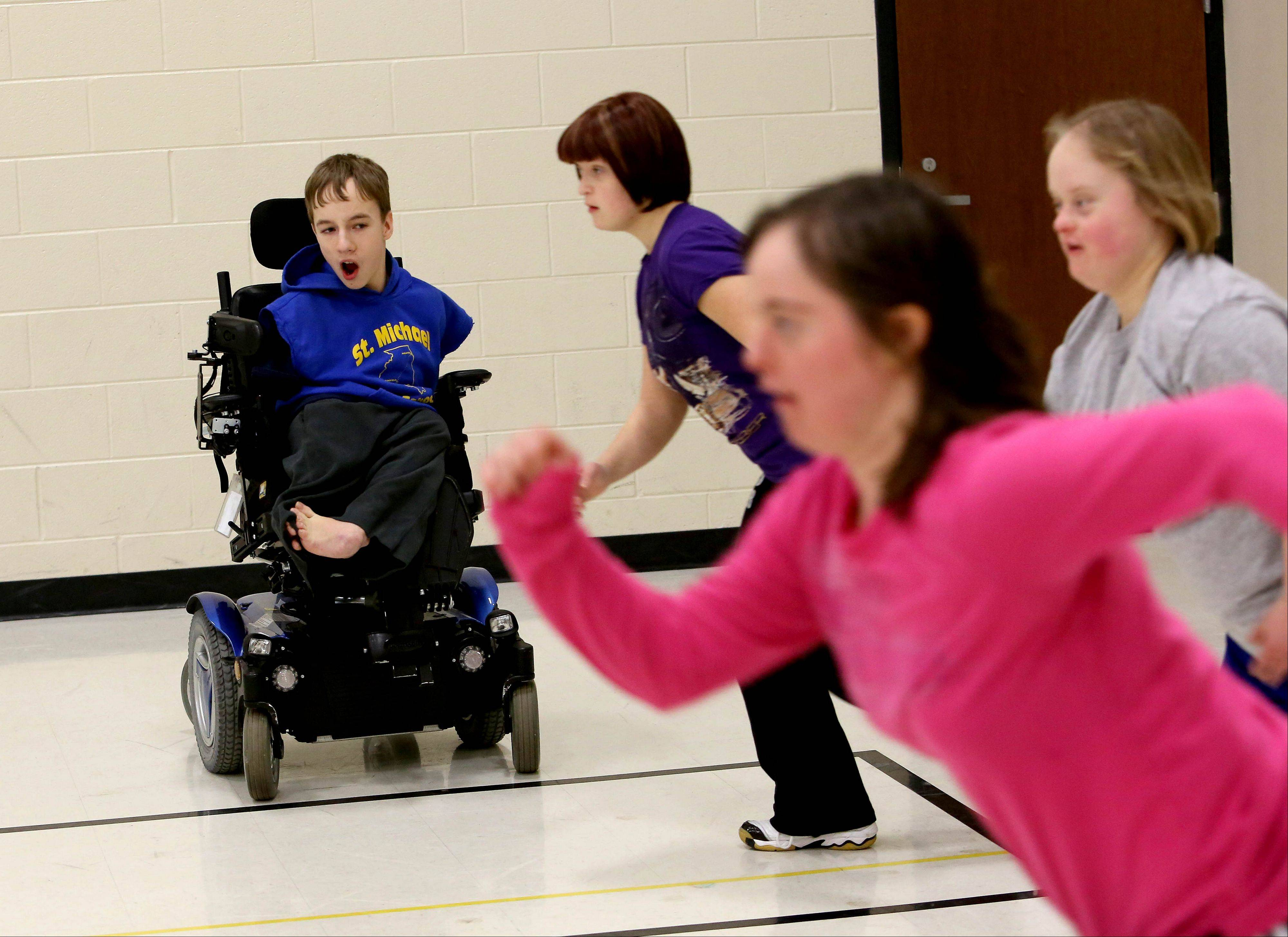 Connor McHugh, 13, of Wheaton encourages sprinters while helping the Special Olympics basketball and track teams at Hubble Middle School in Warrenville. During the fall, Connor serves as an assistant football coach at his school, St. Michael Parish School in Wheaton.