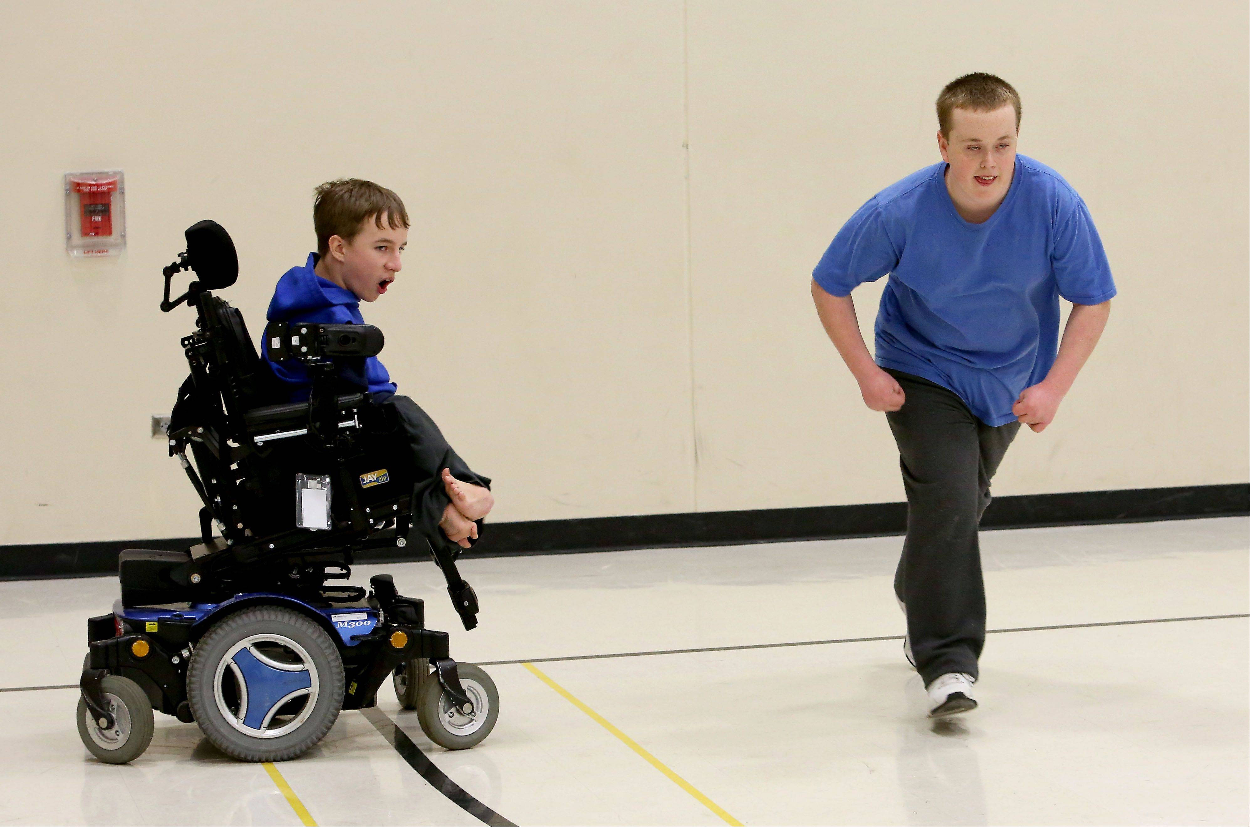 Connor McHugh, left, encourages Alex Starke of Wheaton as he does his sprints for the Special Olympics basketball and track teams at Hubble Middle School in Warrenville.