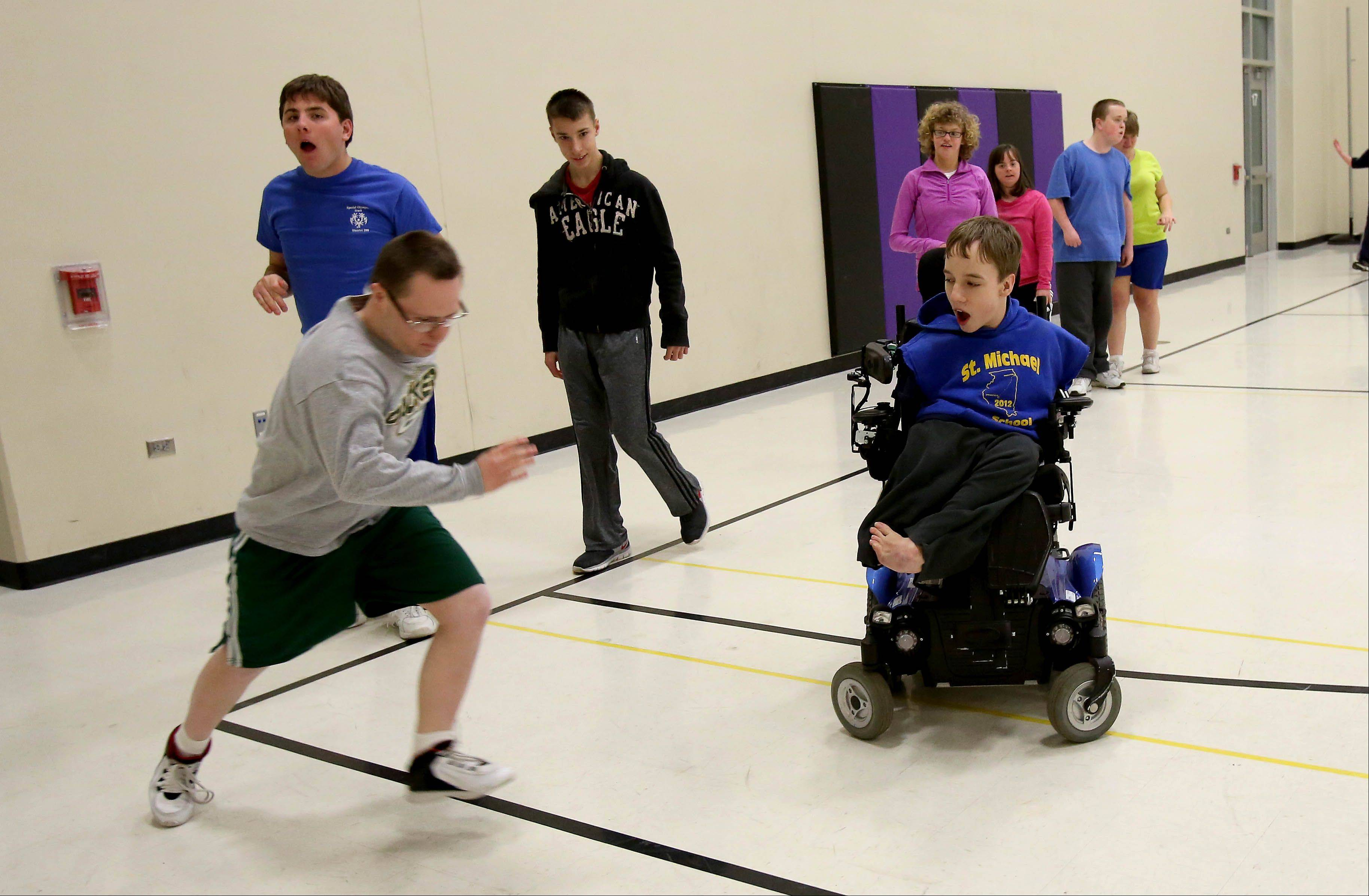 Connor McHugh encourages sprinters as he helps out the Special Olympics basketball and track teams at Hubble Middle School in Warrenville.