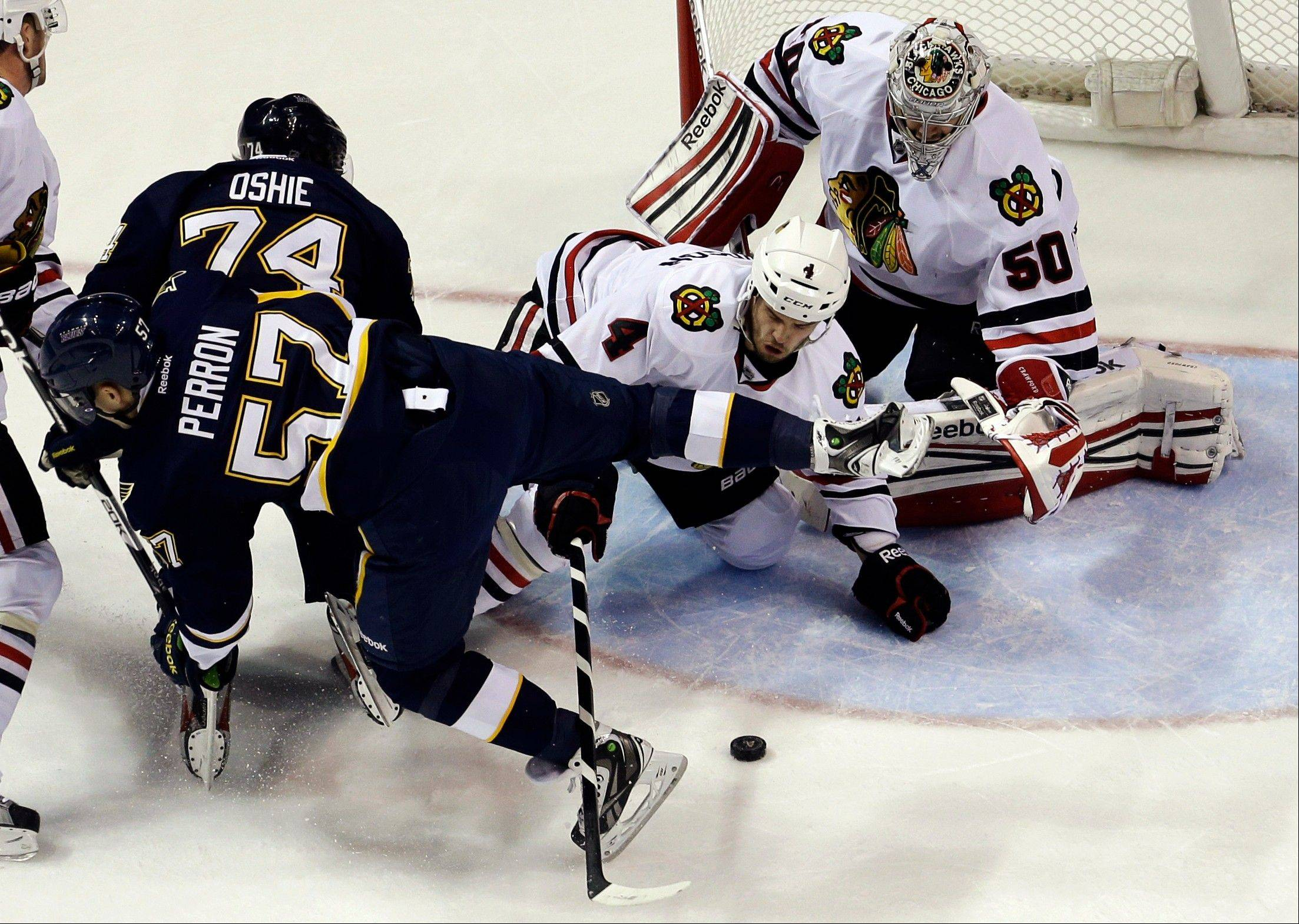 Chicago Blackhawks goalie Corey Crawford and Niklas Hjalmarsson try to smother a loose puck as St. Louis Blues' David Perron, front left, and T.J. Oshie get in on the play during the first period.