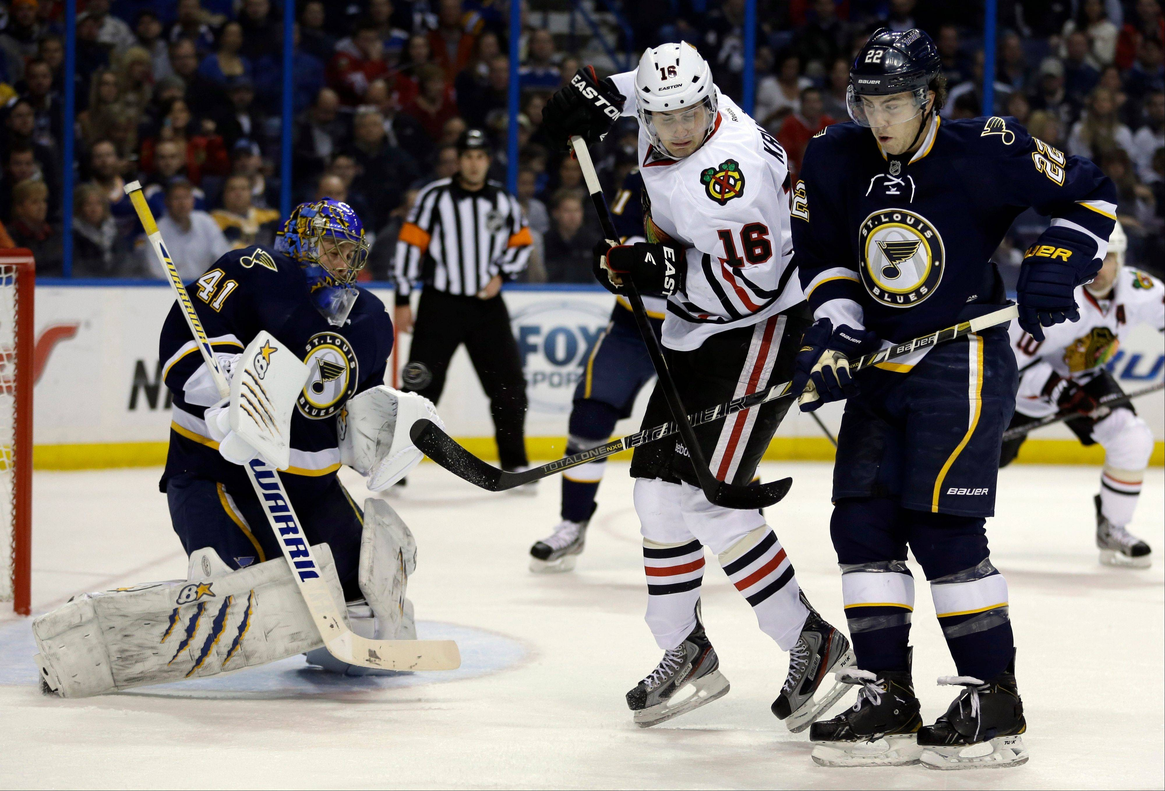 St. Louis Blues goalie Jaroslav Halak deflects the puck as it flies past Chicago Blackhawks' Marcus Kruger, center, and Blues' Kevin Shattenkirk, right, during the first period.