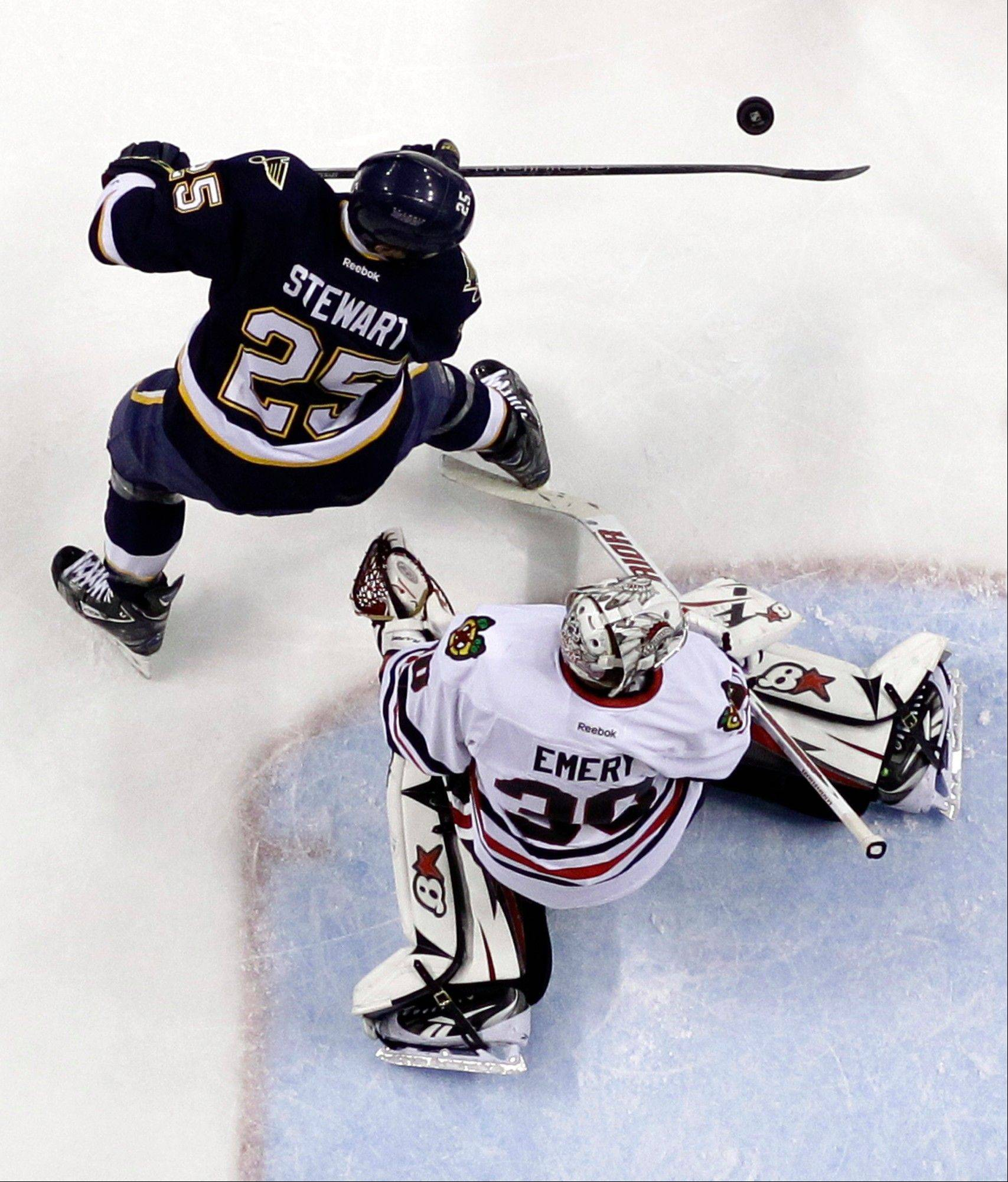 St. Louis Blues' Chris Stewart, top, tries to reach the puck as Chicago Blackhawks goalie Ray Emery defends during the second period.