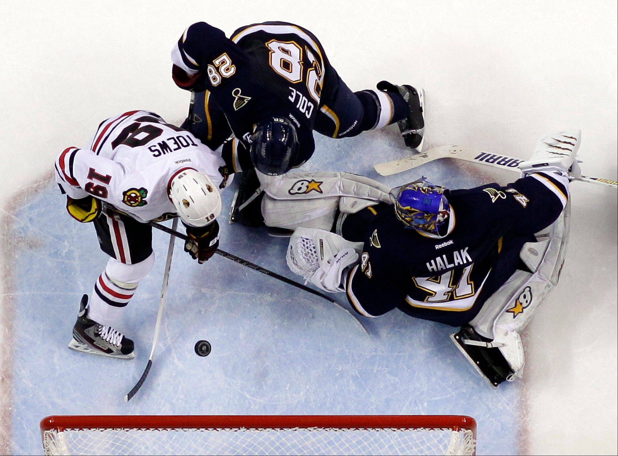 Chicago Blackhawks' Jonathan Toews, left, scores his second goal of an NHL hockey game as St. Louis Blues goalie Jaroslav Halak and Ian Cole, center, defend.