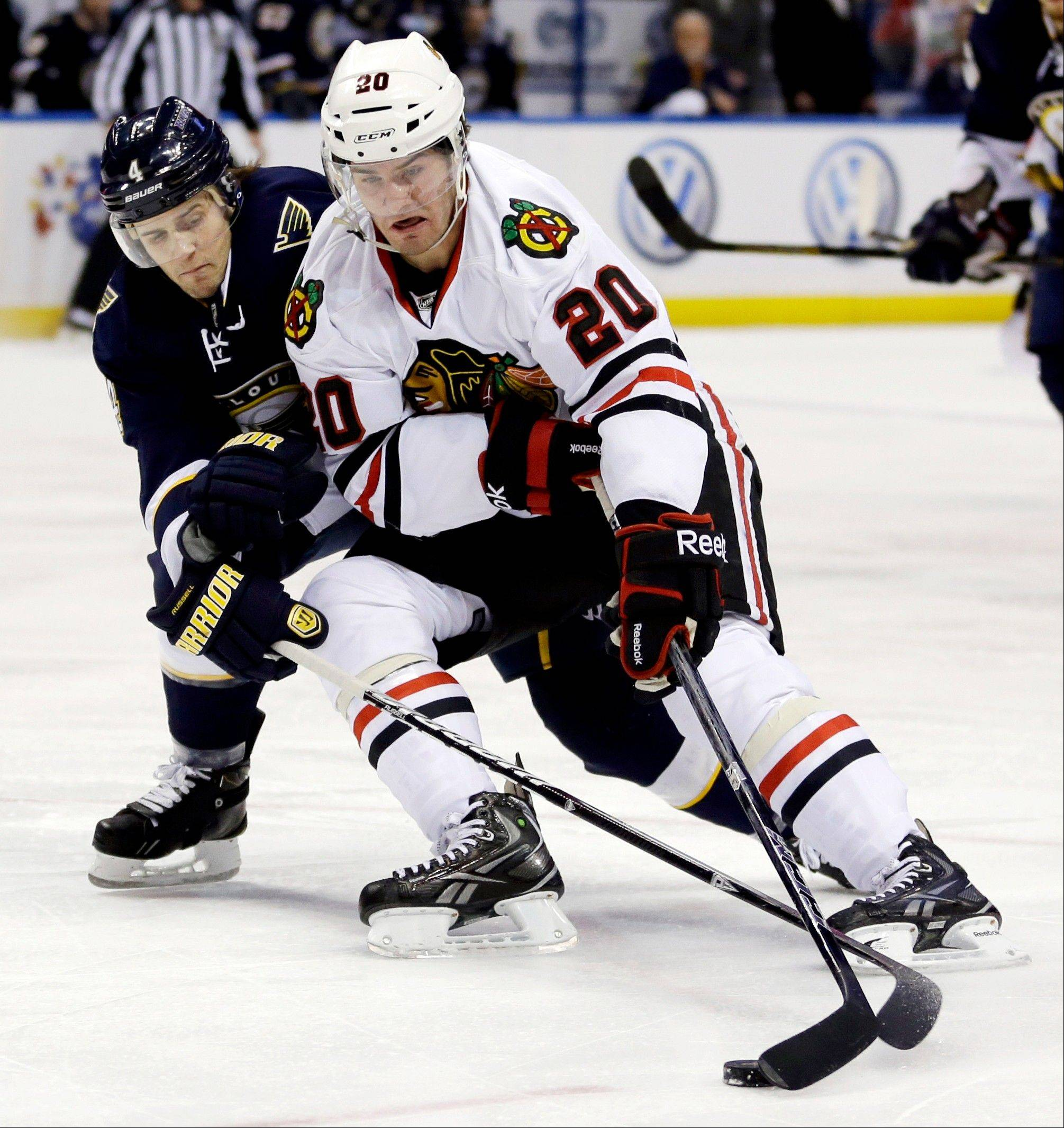 Chicago Blackhawks' Brandon Saad tries to slip past St. Louis Blues' Kris Russell during the first period.