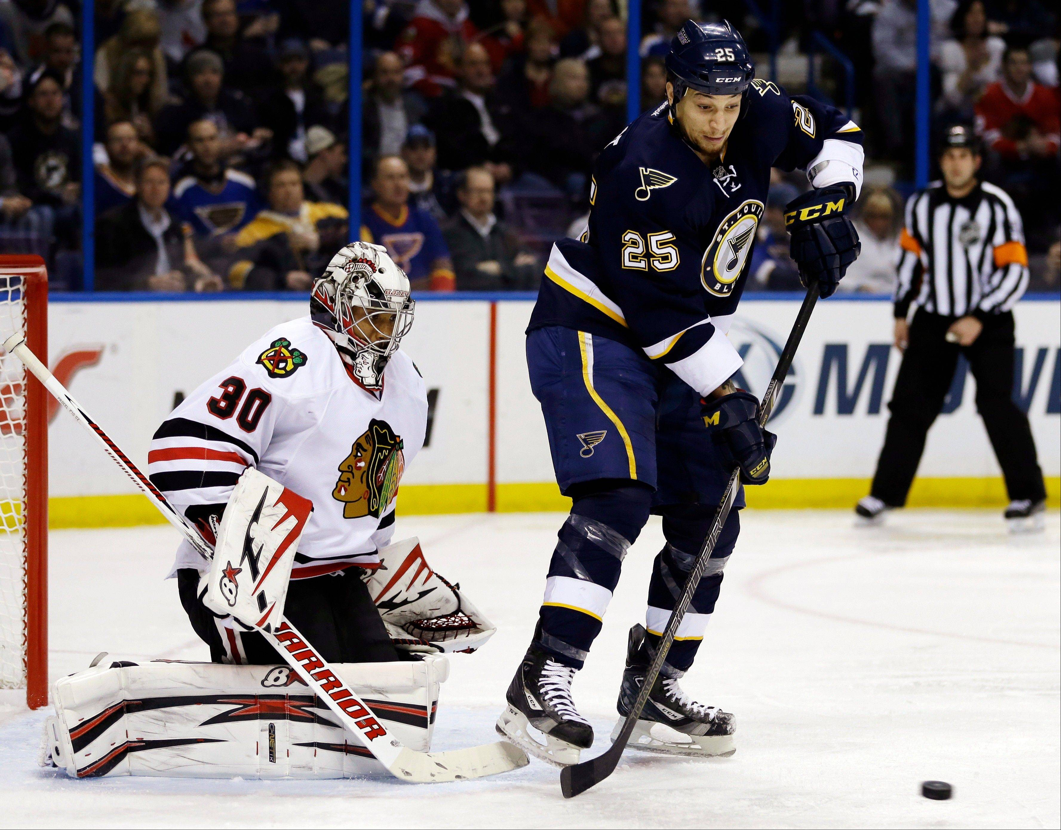 St. Louis Blues' Chris Stewart tries to deflect a puck as Chicago Blackhawks goalie Ray Emery defends during the second period .