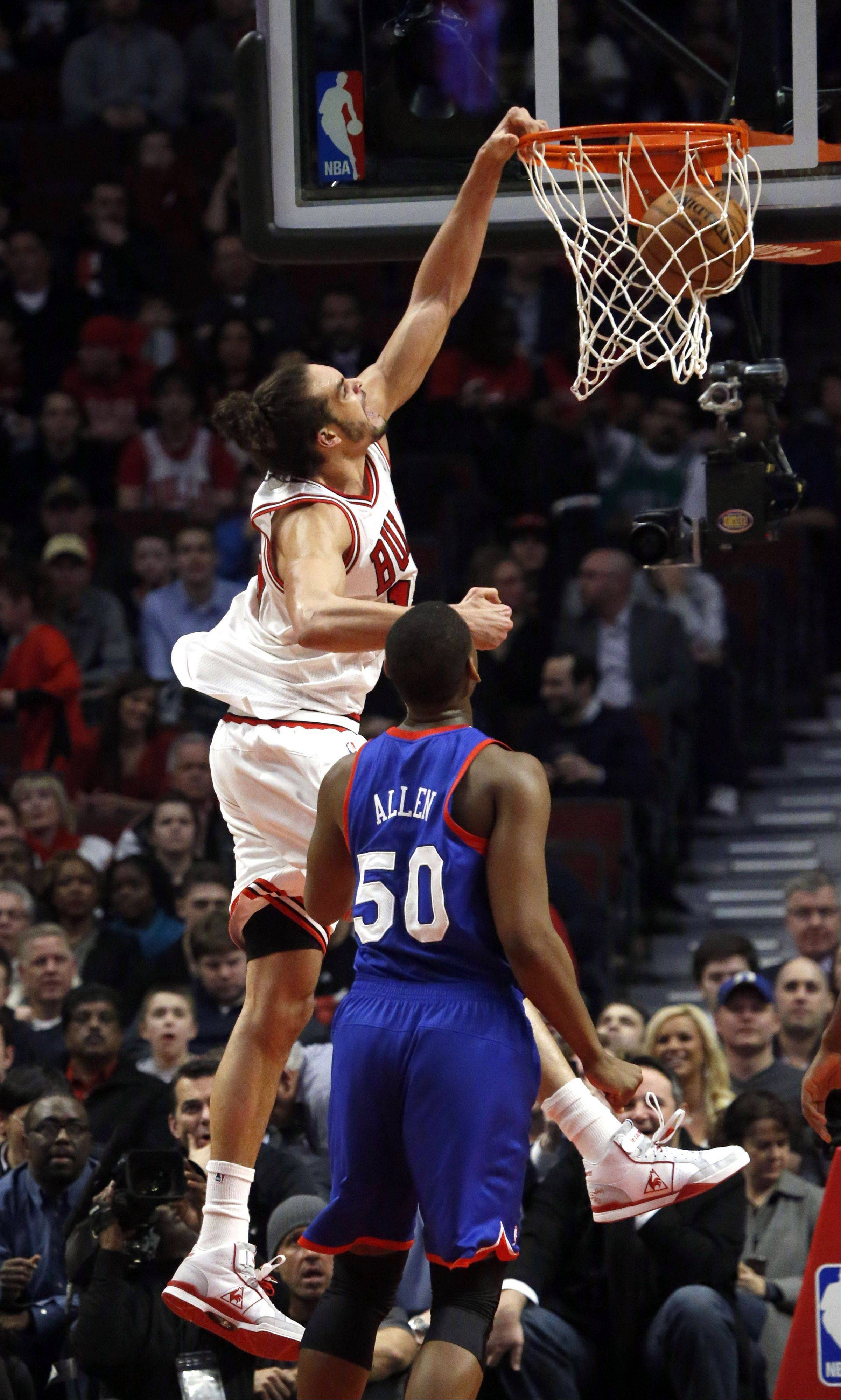 Chicago Bulls center Joakim Noah (13) dunks past Philadelphia 76ers forward Lavoy Allen (50) during the first half of an NBA basketball game, Thursday, Feb. 28, 2013, in Chicago.