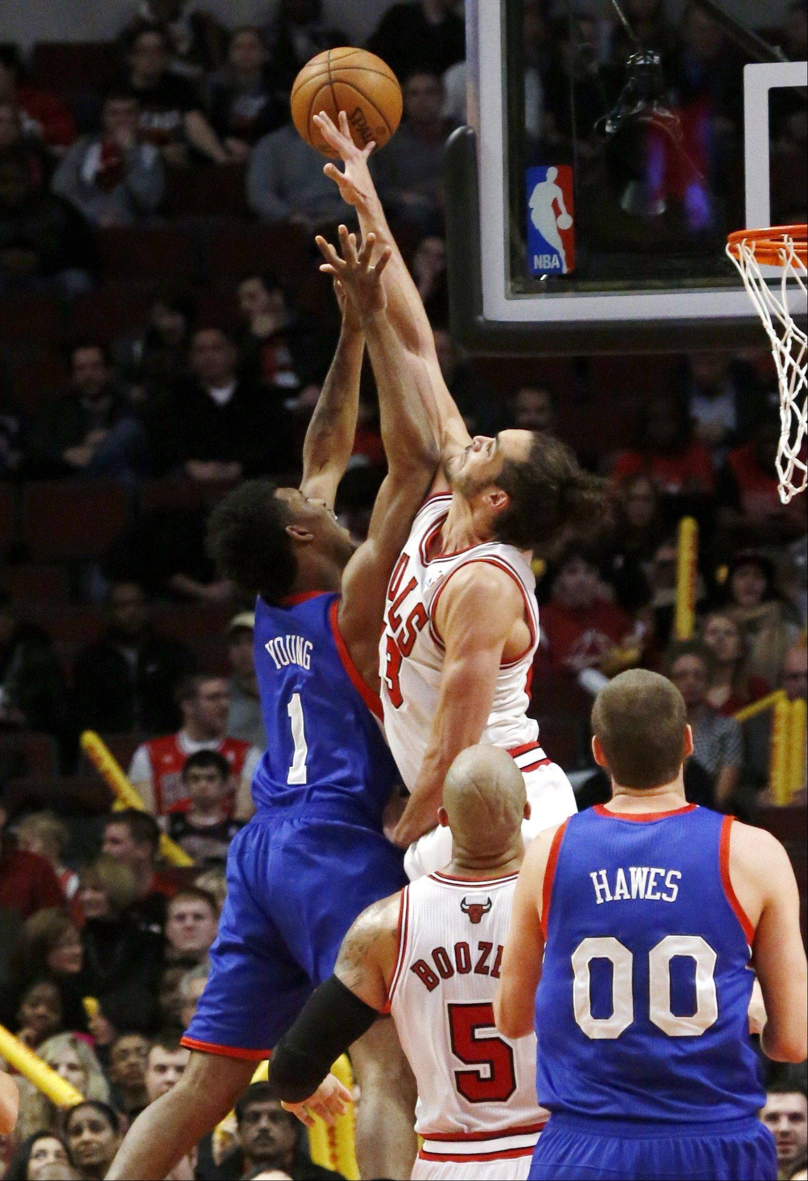Bulls center Joakim Noah blocks the shot of Philadelphia 76ers guard Nick Young (1) as Spencer Hawes (00) and Bulls' Carlos Boozer (5) watch during the second half of Thursday night's game. Noah recorded a triple double of 23 points, 21 rebounds and 11 blocked shots as the Bulls won 93-82.