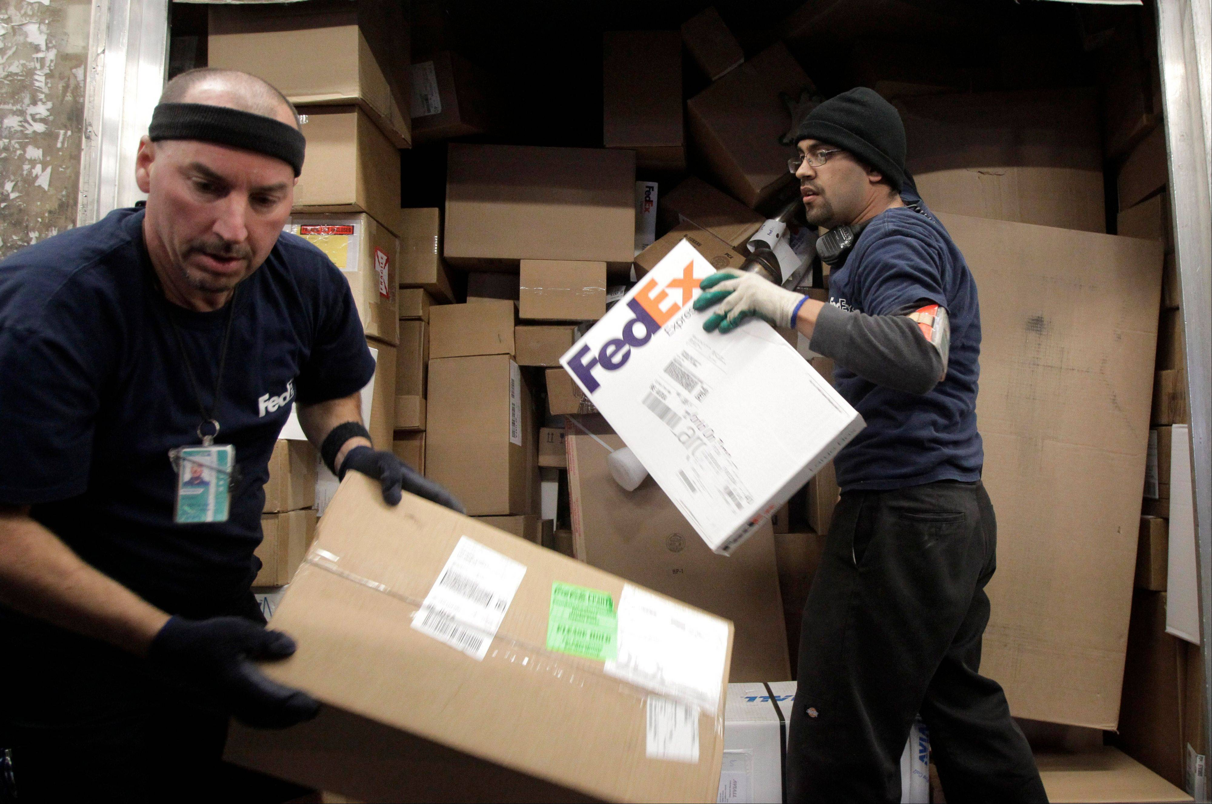 Associated Press/Dec. 13, 2011 FedEx workers unload packages at the FedEx hub at Los Angeles International Airport in Los Angeles.