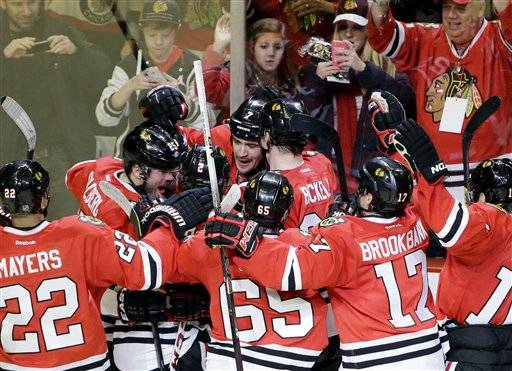 Brent Seabrook, center, celebrates with teammates after scoring his game-winning goal during the overtime Friday at teh United Center.