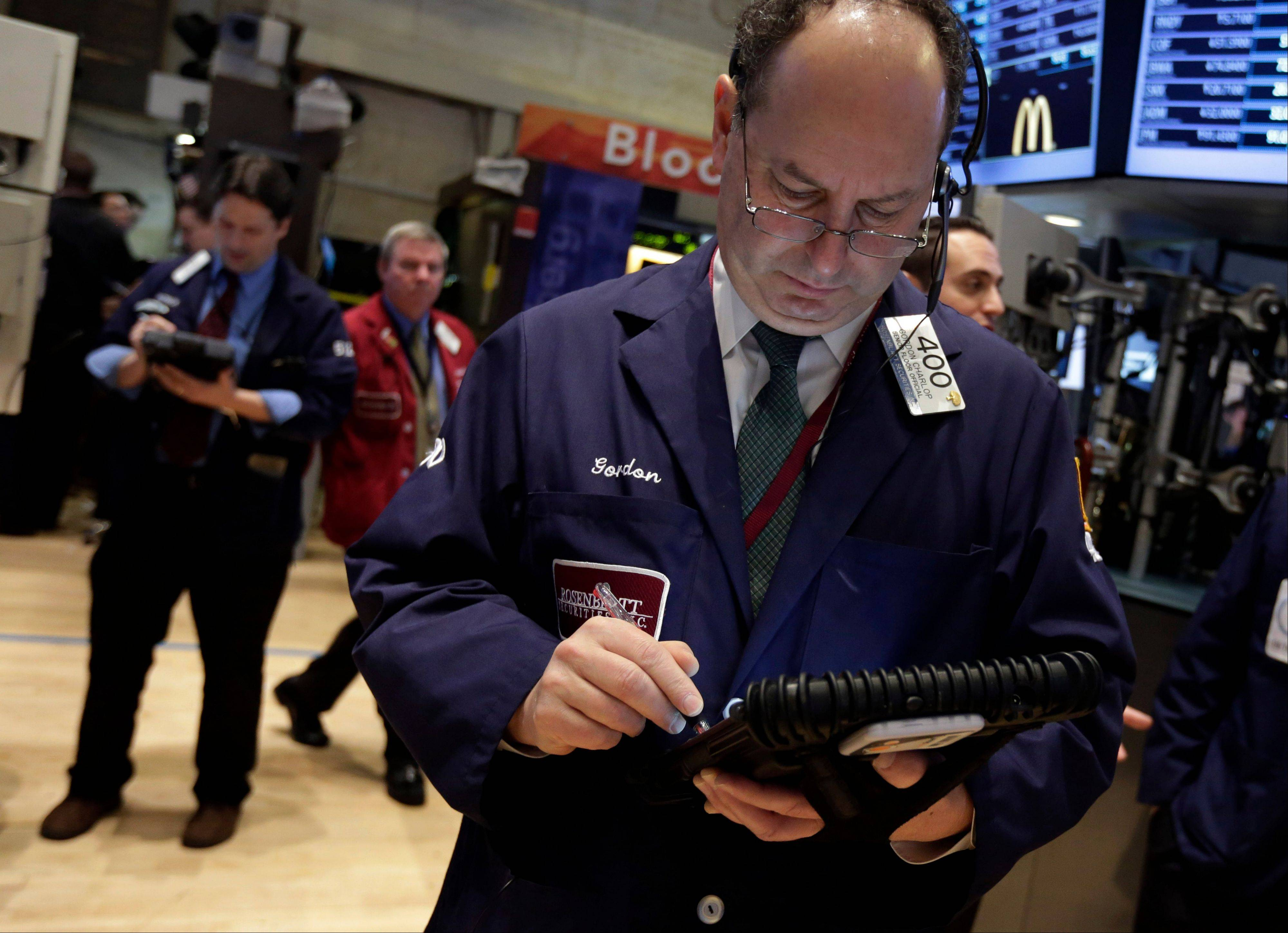 Gordon Charlop, right, works Thursday on the floor of the New York Stock Exchange.