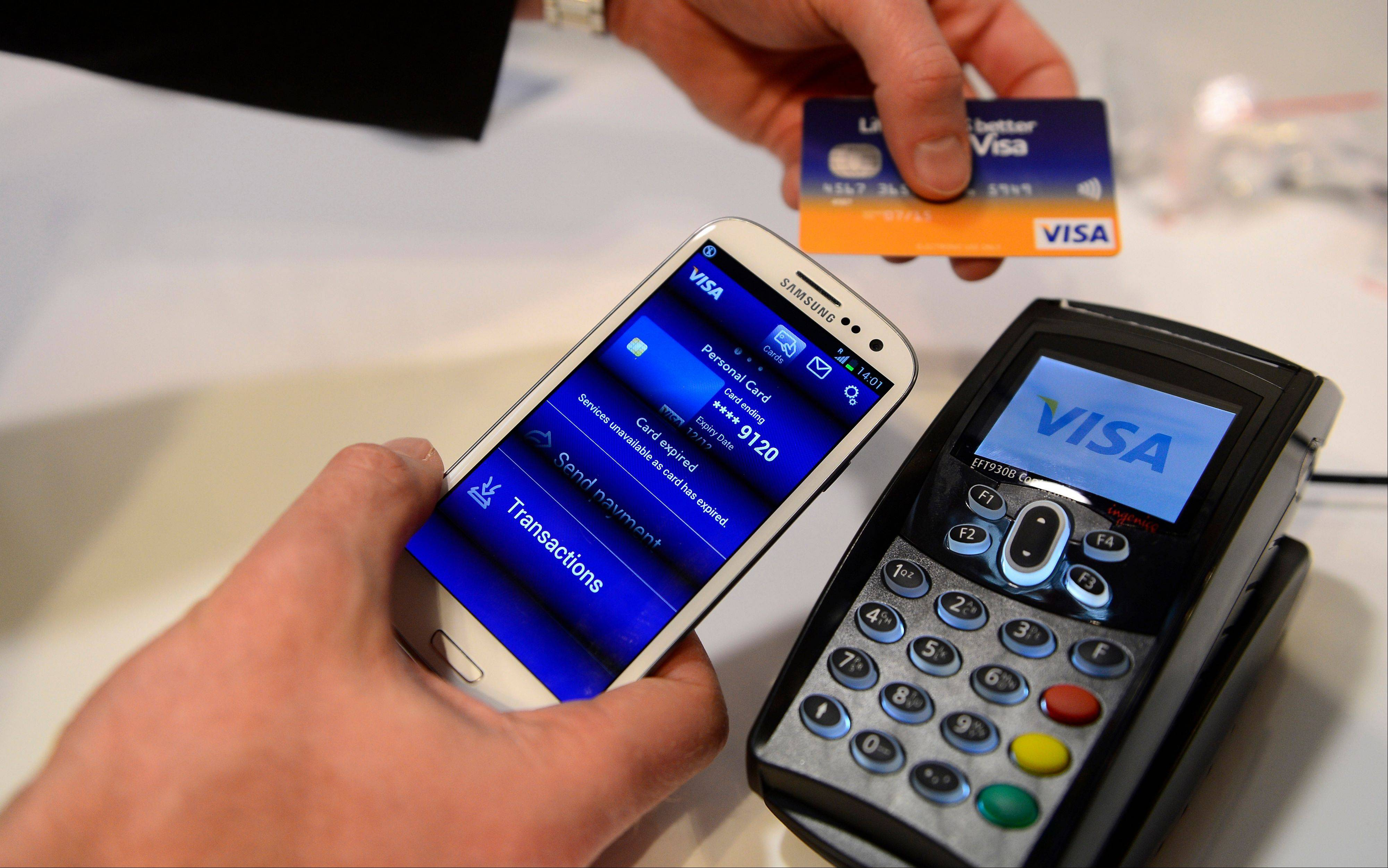A man uses the NFC payment Visa system at the Mobile World Congress, the world's largest mobile phone trade show, in Barcelona, Spain.