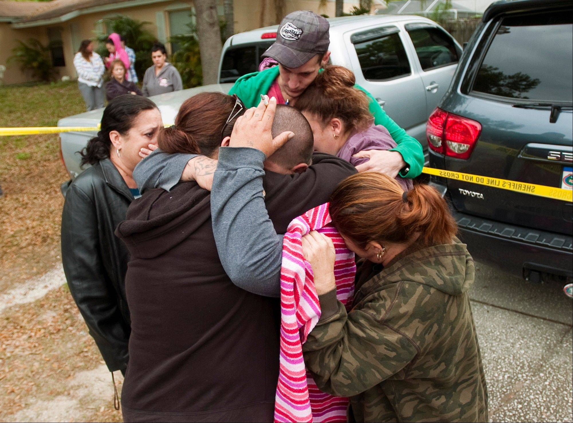 Jeremy Bush, center with hand on head, is embraced Friday by family and friends outside his home at 420 Faithway Drive in Seffner, Fla.