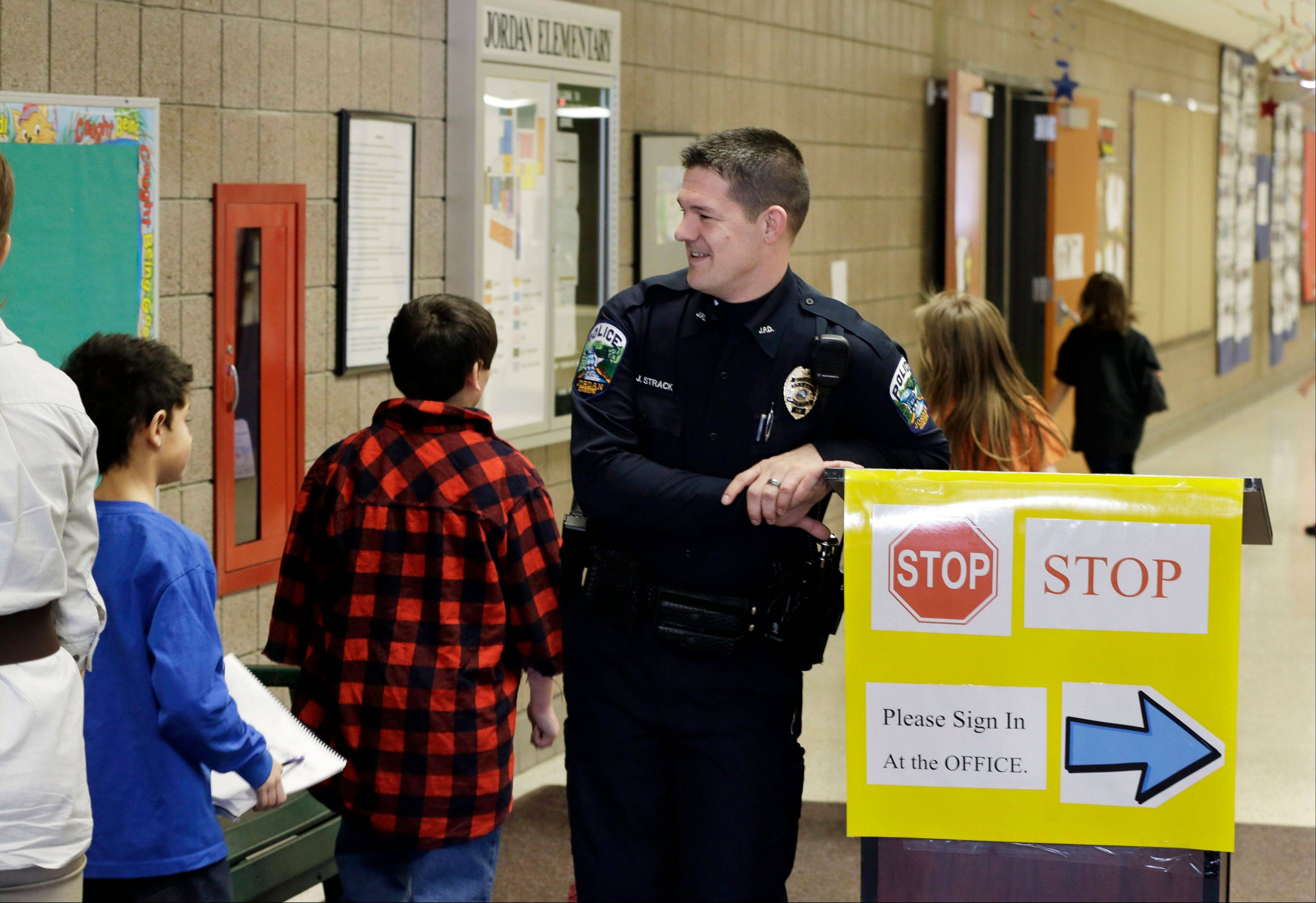 Police officer Jeff Strack smiles at children changing classrooms Thursday at Jordan Elementary School in Jordan, Minn.