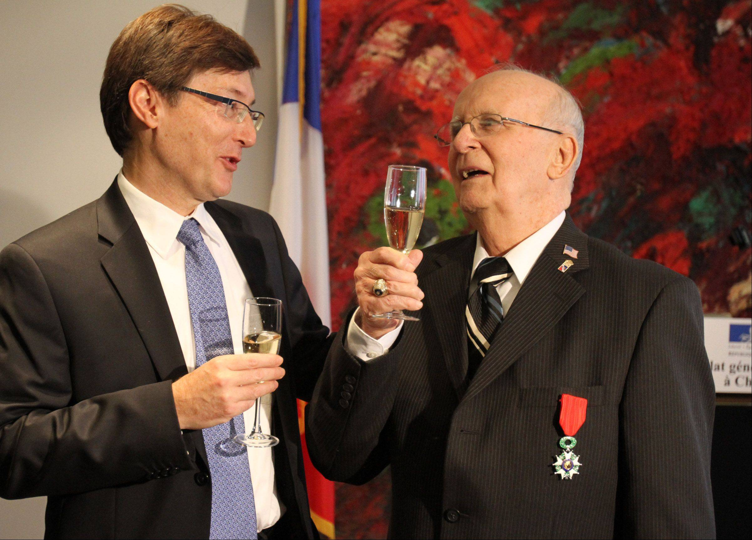 Jim Butz of Schaumburg and Consul Graham Paul hold a champagne toast after Paul presented Butz with the Legion of Honor medal at the Consulate General of France in Chicago on Friday.