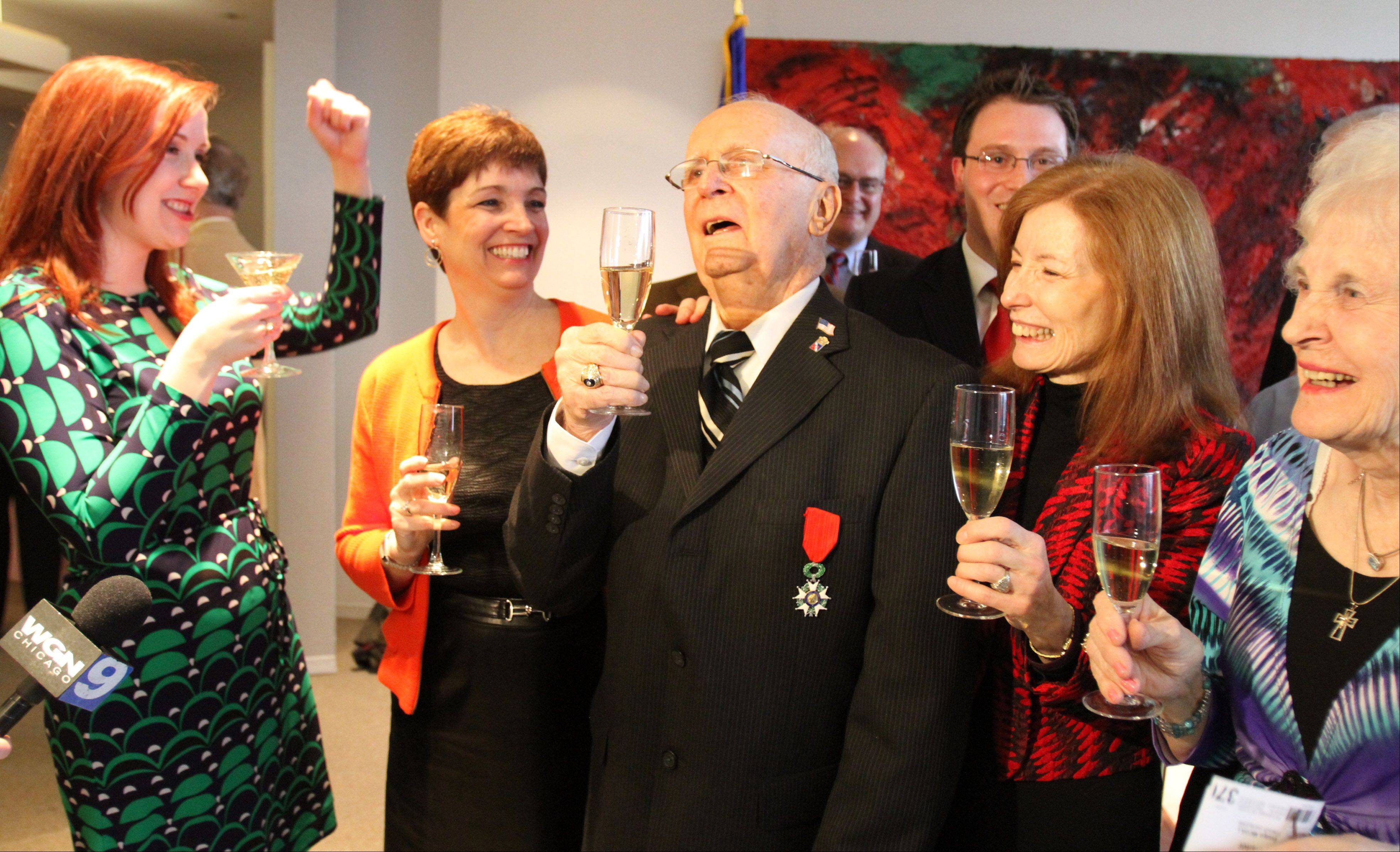 Jim Butz of Schaumburg and his family, including granddaughter Kerry Butz of Elk Grove Village at far left, toast with champagne after he received the French Legion of Honor medal Friday at French Consulate in Chicago.