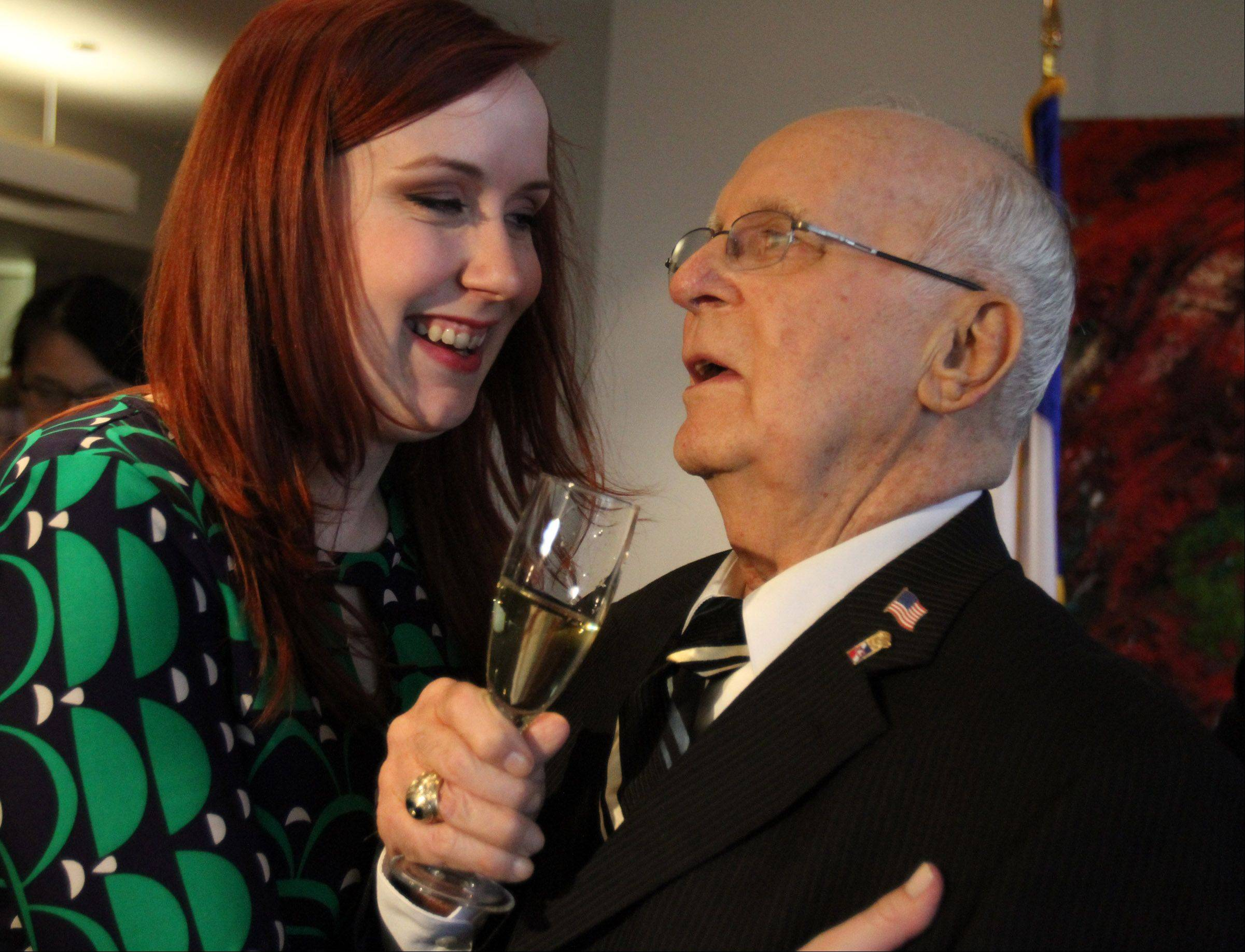 Jim Butz of Schaumburg receives a hug from his granddaughter Kerry Butz of Elk Grove Village after he received the French Legion of Honor medal at the Consulate General of France in Chicago on Friday.